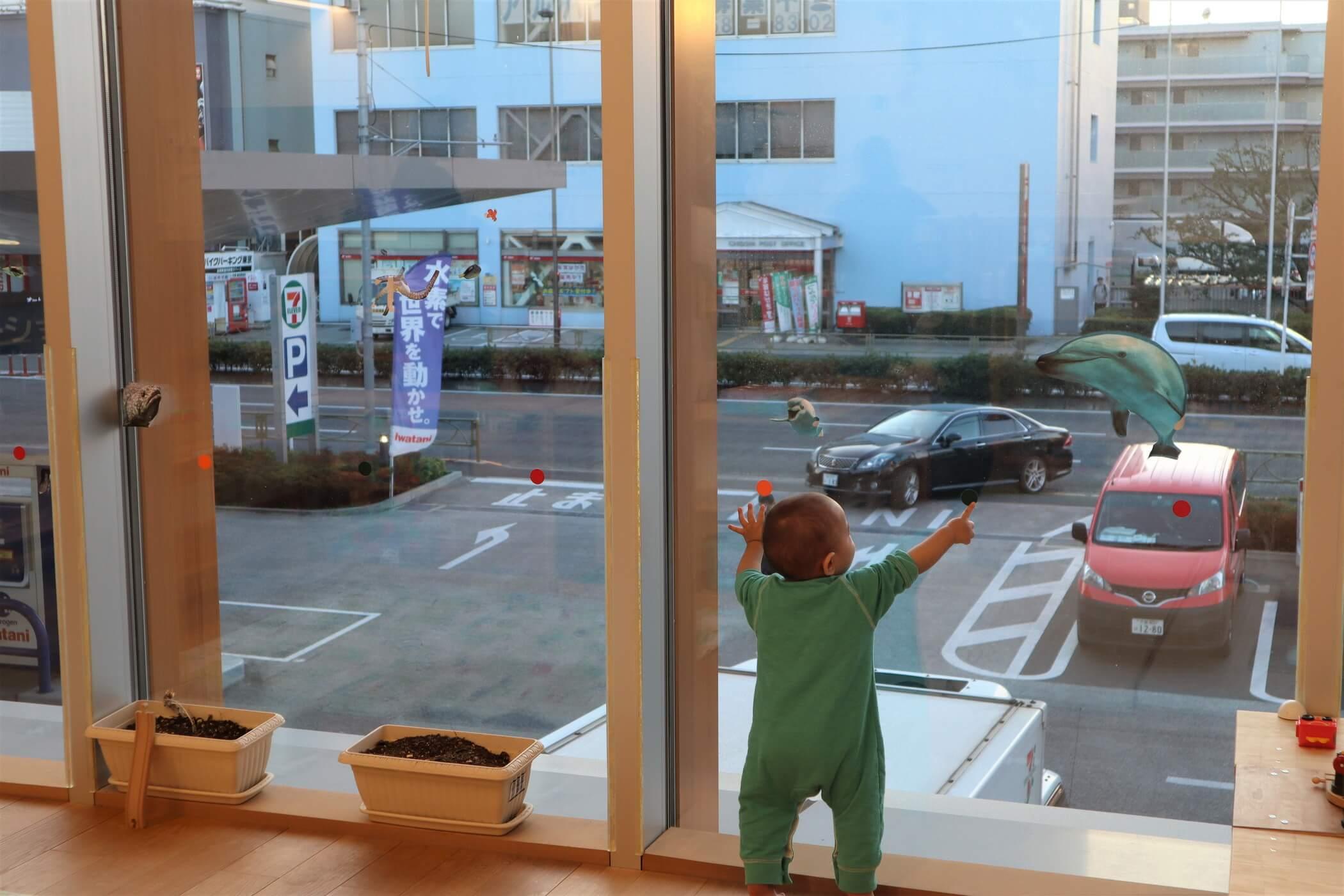 大きな窓辺で遊ぶ乳児