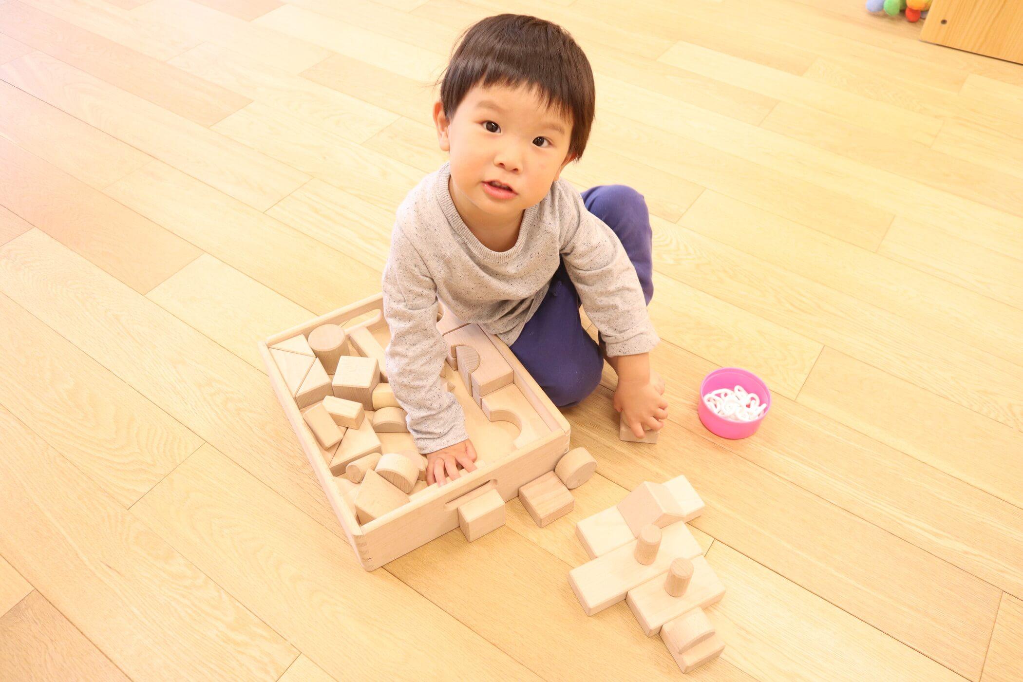 積み木で見立て遊びをする園児