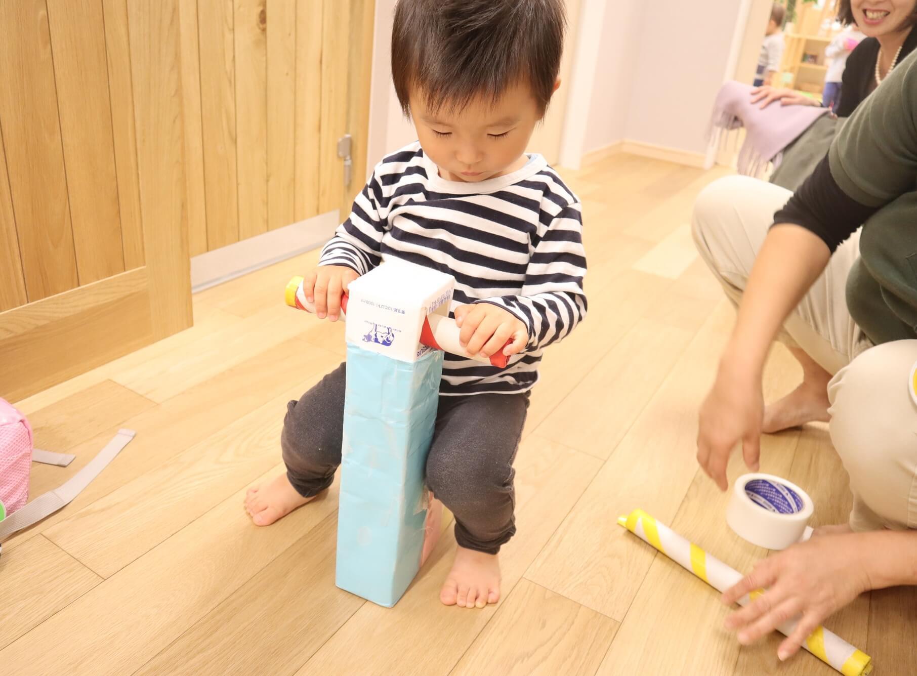 牛乳パックで作った乗り物で遊ぶ園児