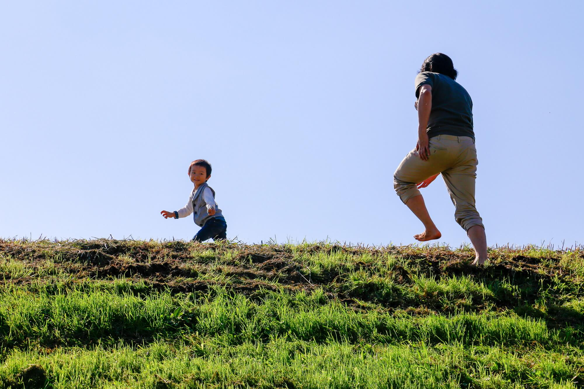 子どもと土手で追いかけっこをする職員