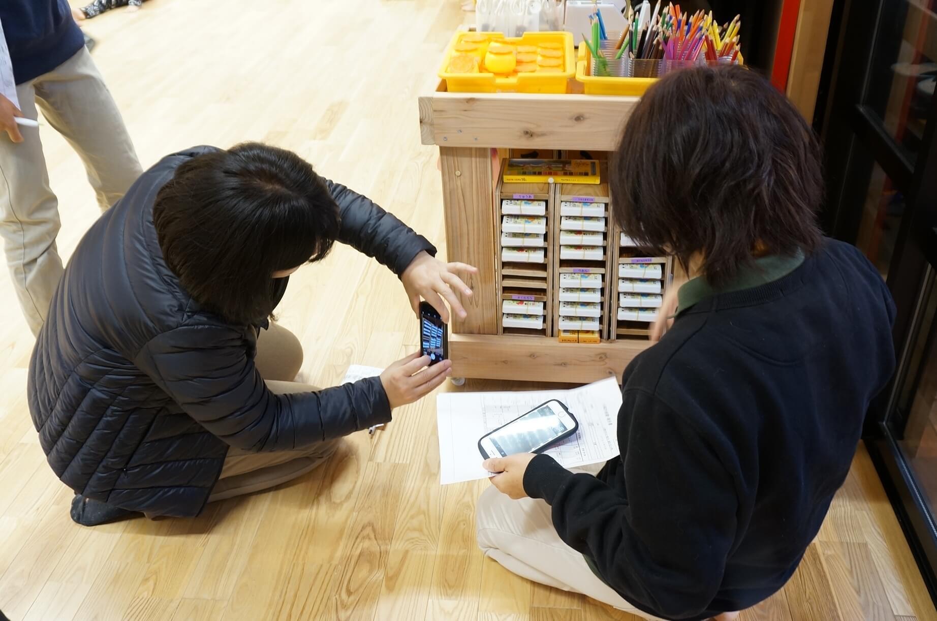 手作りの棚を撮影する職員