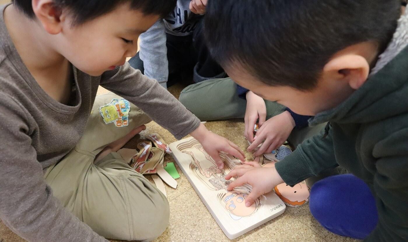 木製人体パズルをする男の子グループ