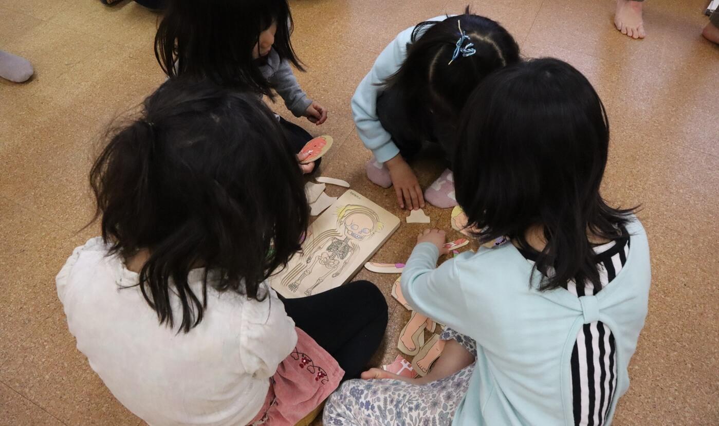 木製人体パズルをする女の子グループ