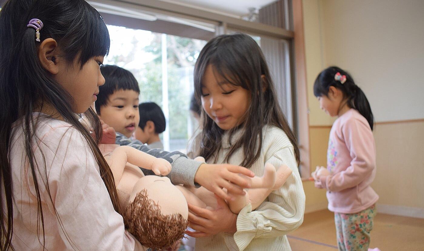 ももちゃん人形を抱っこする園児