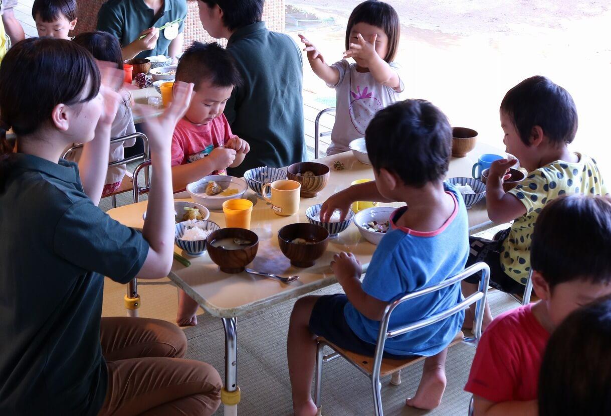 見学会で園児と給食を食べる参加者