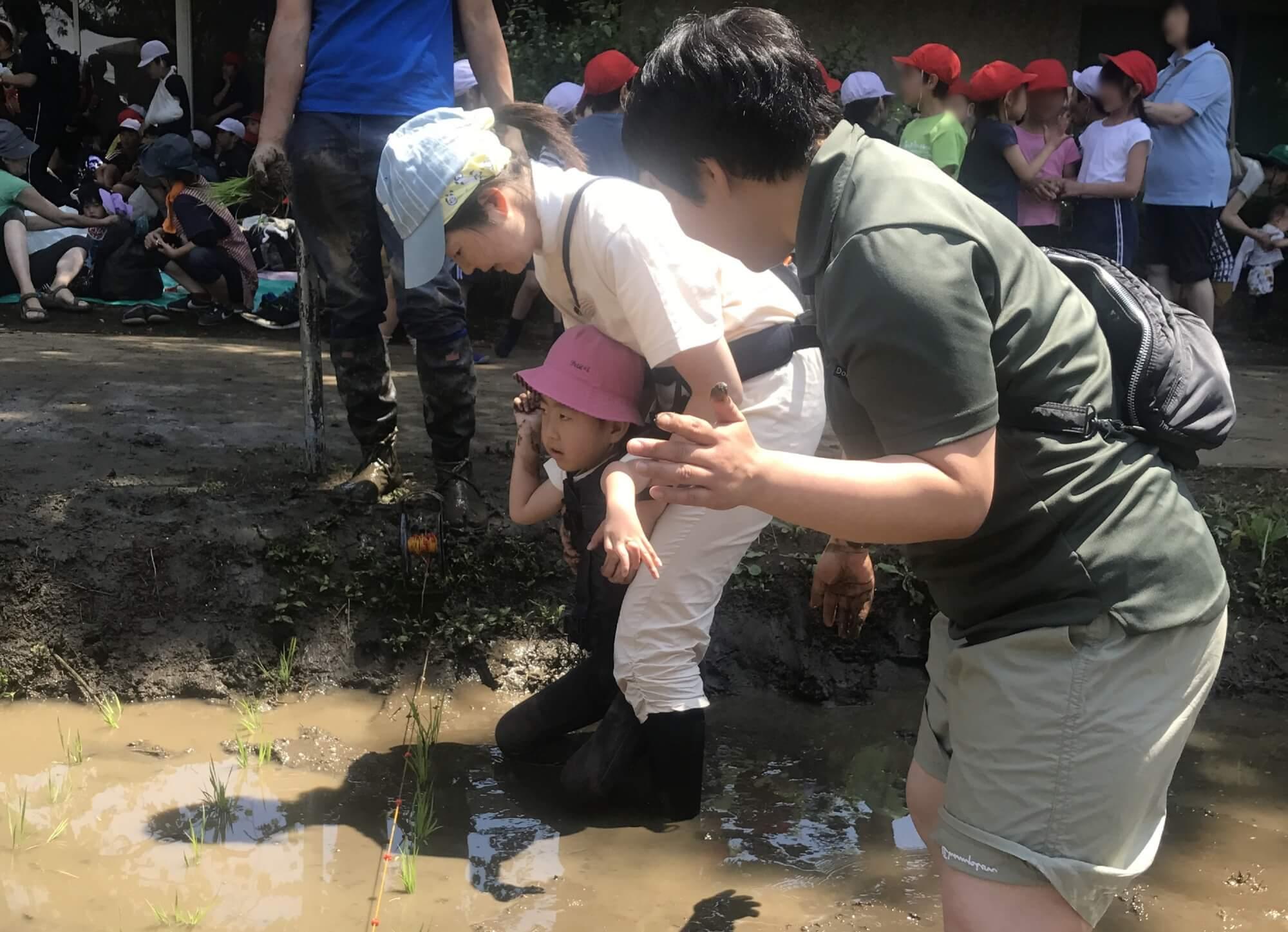お母さんに支えられて泥の感触を感じる
