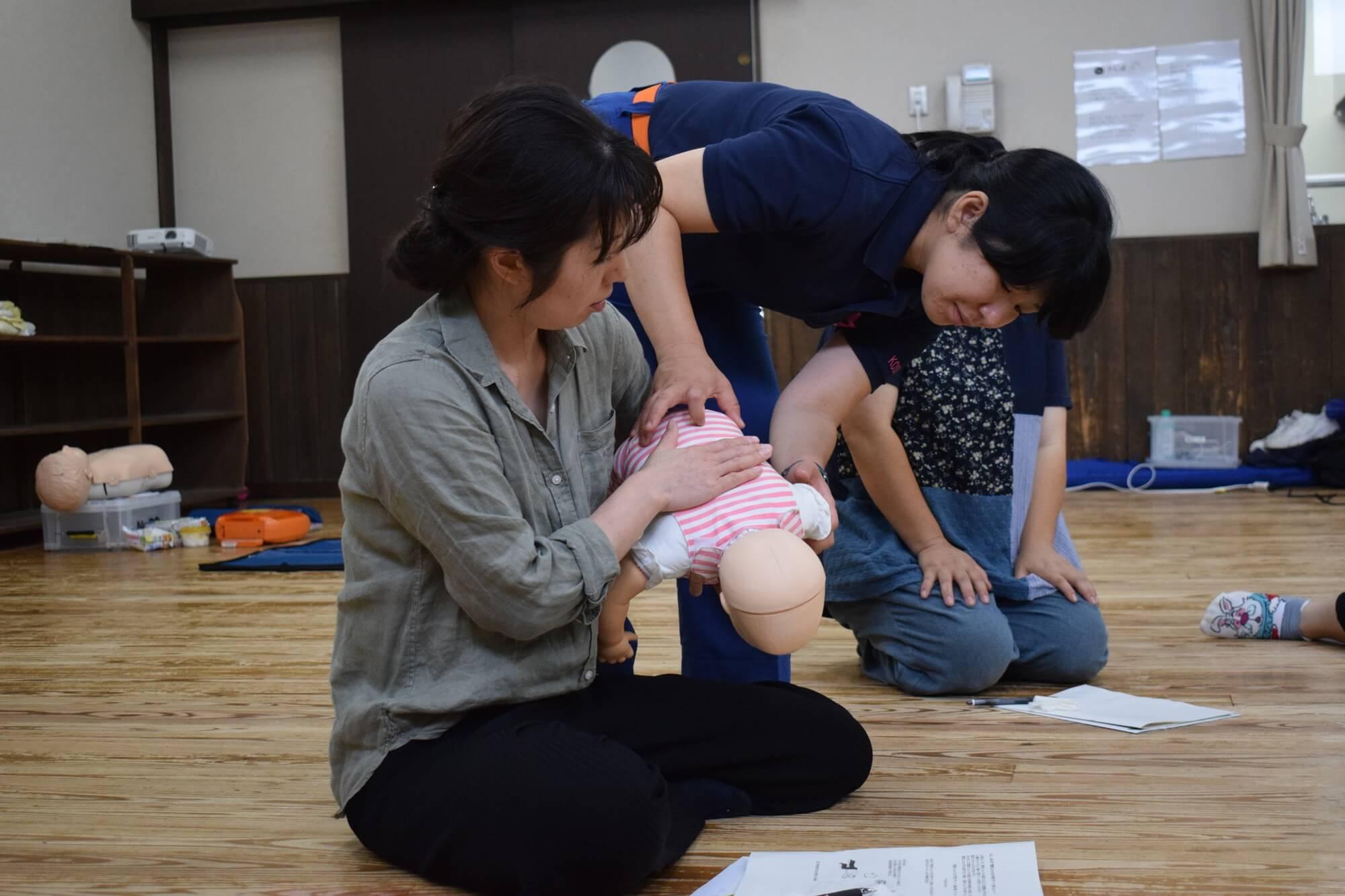 乳児の誤飲・窒息時の背部叩打法を体験する参加者