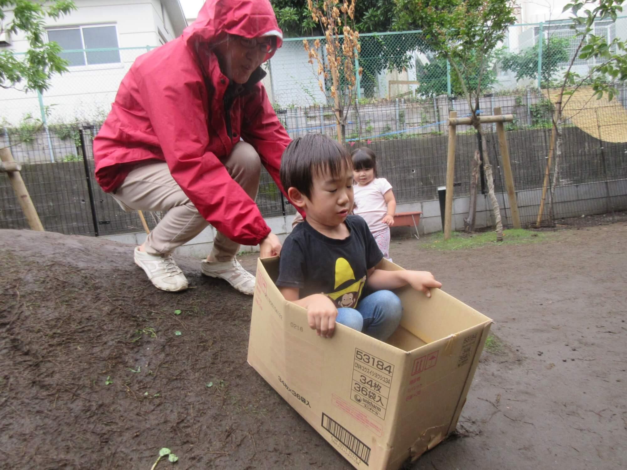 築山を段ボール箱で滑る子ども