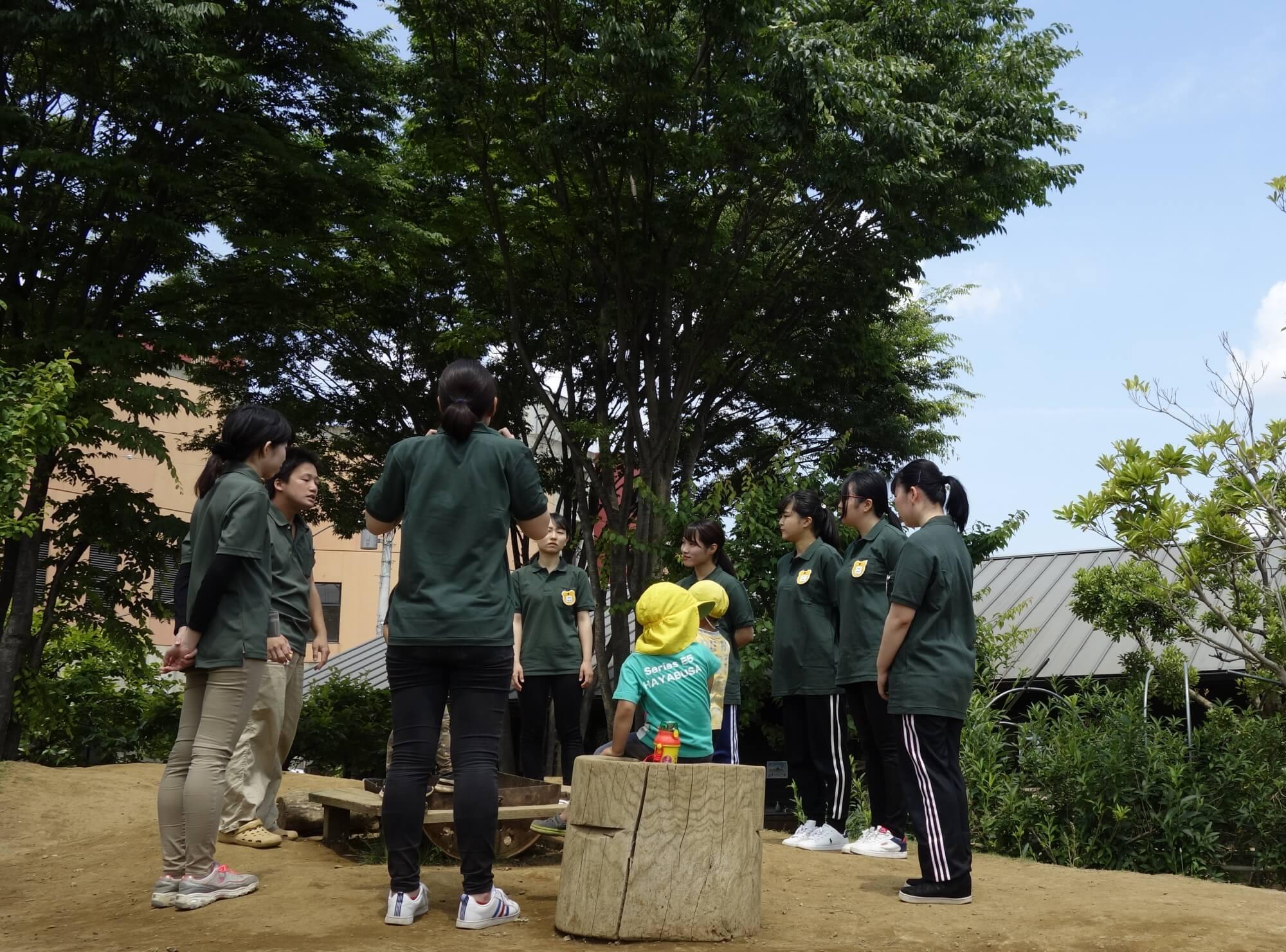 園を保育学生に案内する保育士