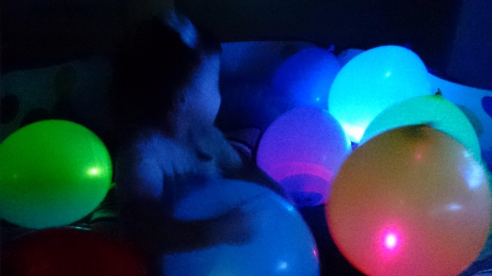 暗い部屋の中で光る風船で遊ぶ子ども