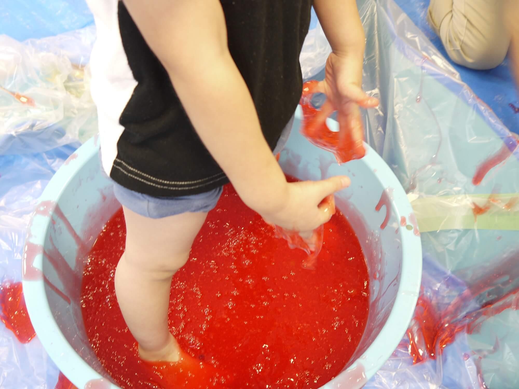 赤いスライムで遊ぶ子ども