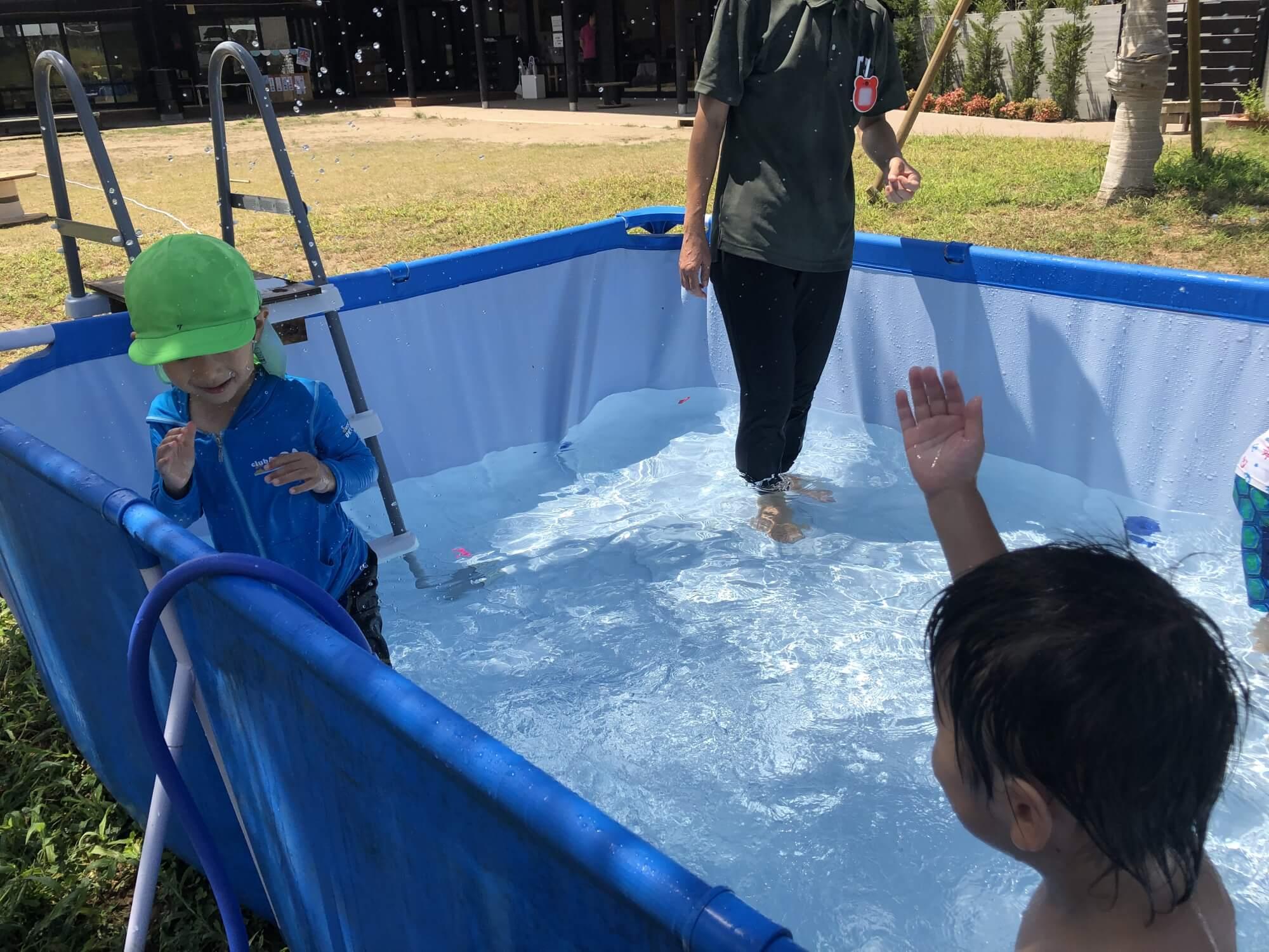 プールで水のかけあいをする子どもたち