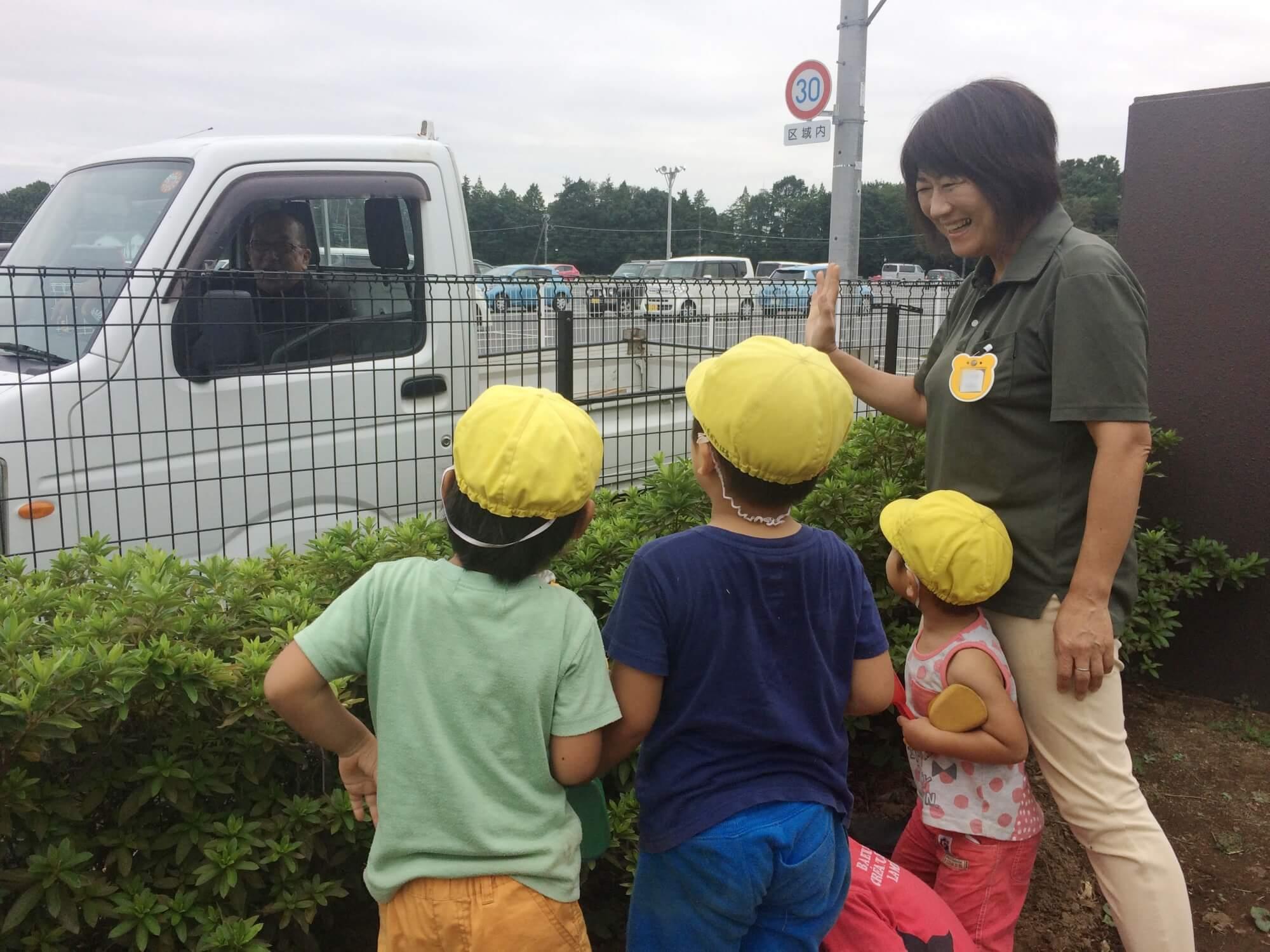 地域のおじさんに手をふる園児たち