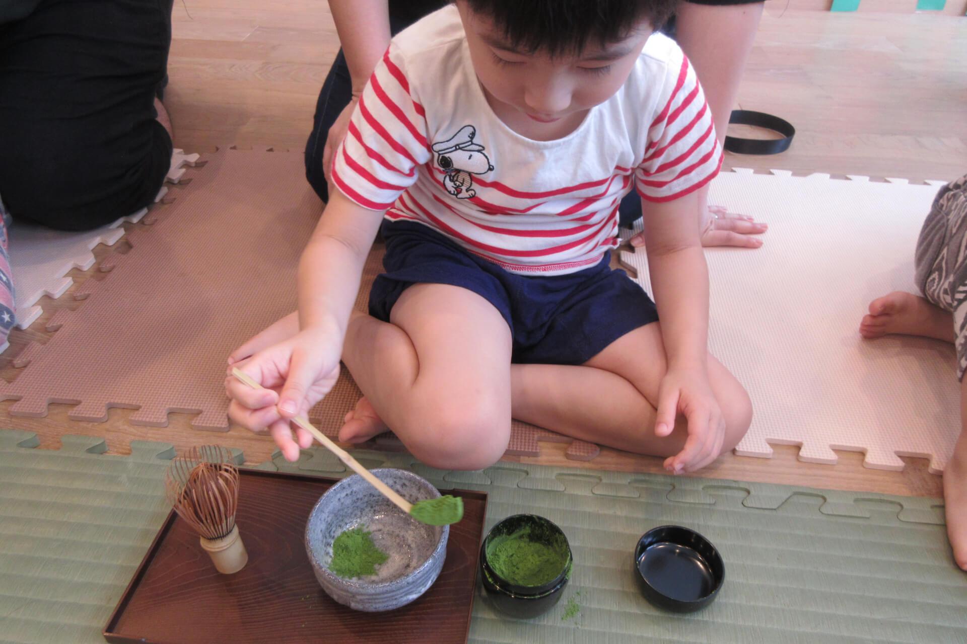 さじで抹茶の粉を入れる子供