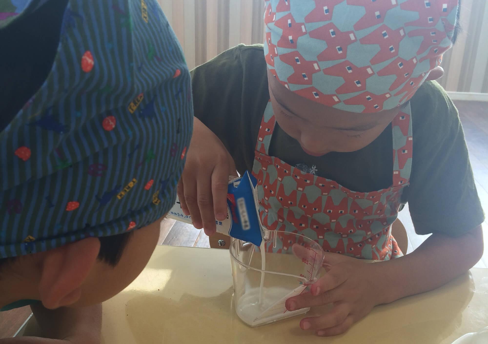 牛乳の量を量る子ども