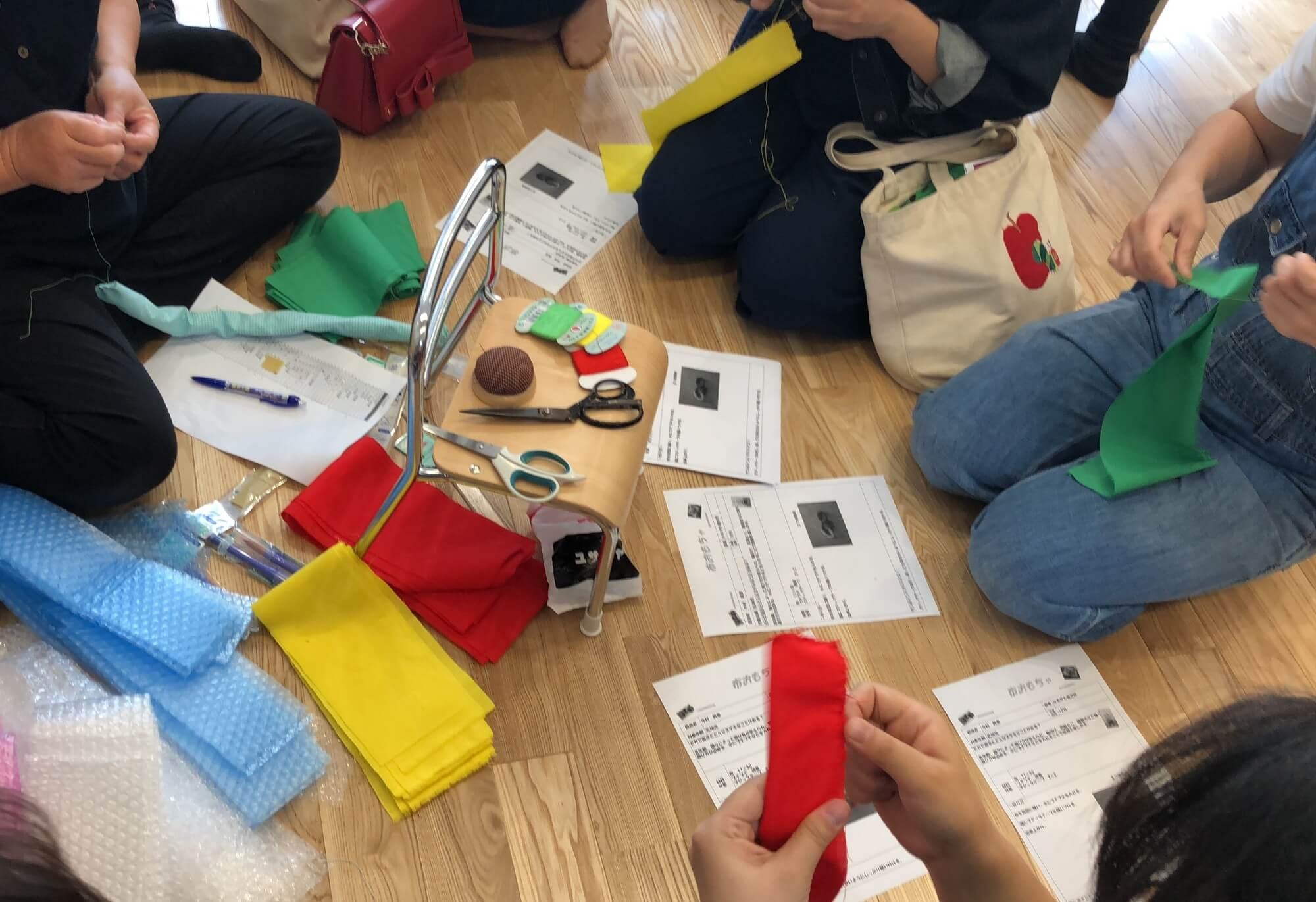 布で手作りおもちゃを作る職員