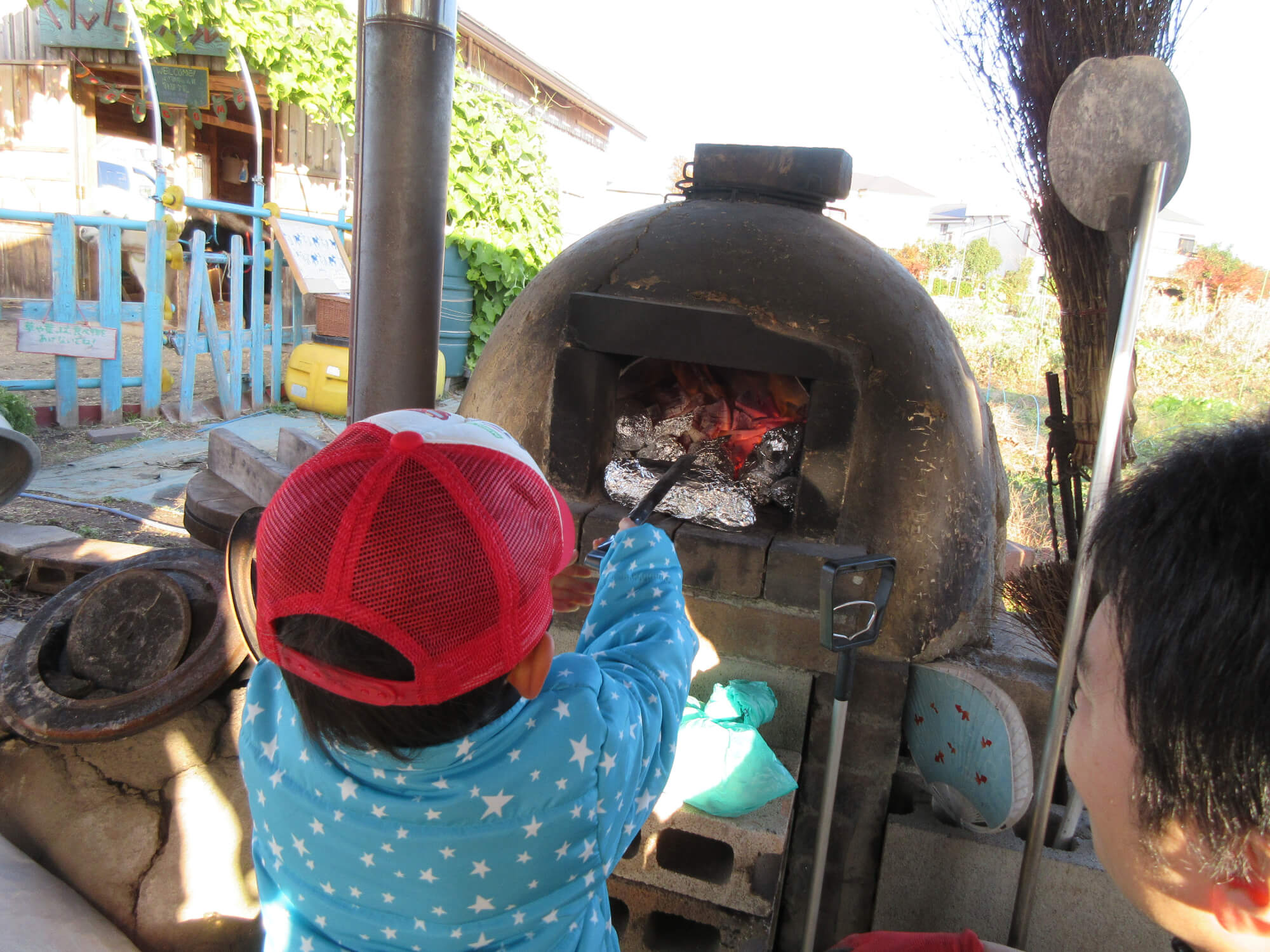 火の中にさつまいもを入れる子ども