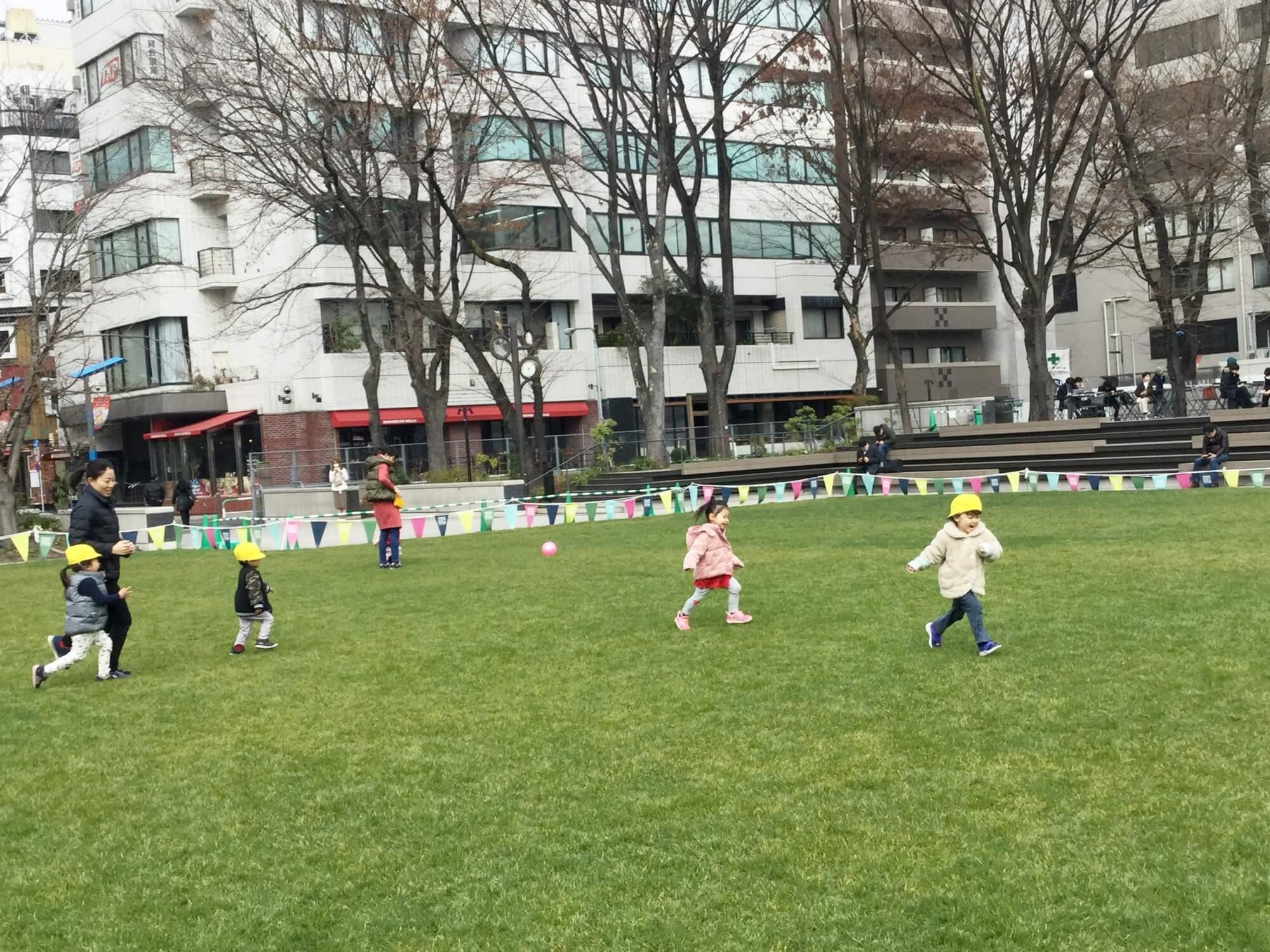 芝生の公園で元気よく駆け回る園児たち