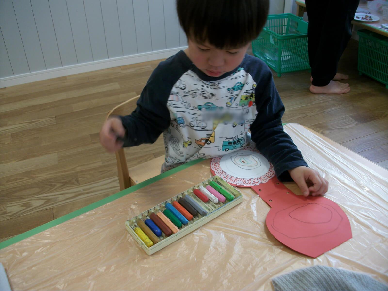 クリスマスカードに絵を描いている子ども