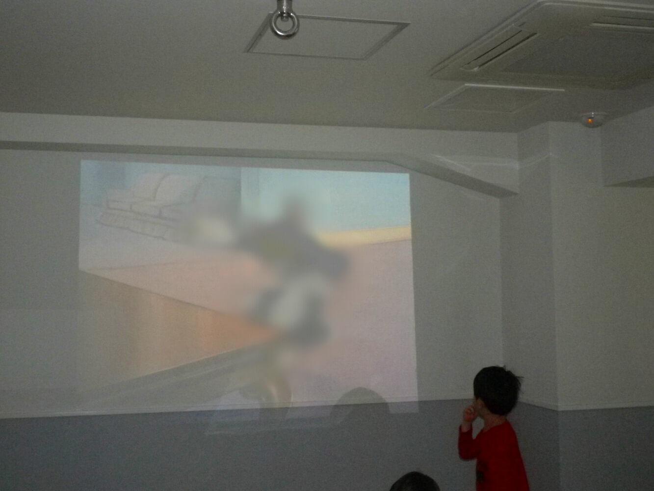 壁に映っている映像をみている子ども