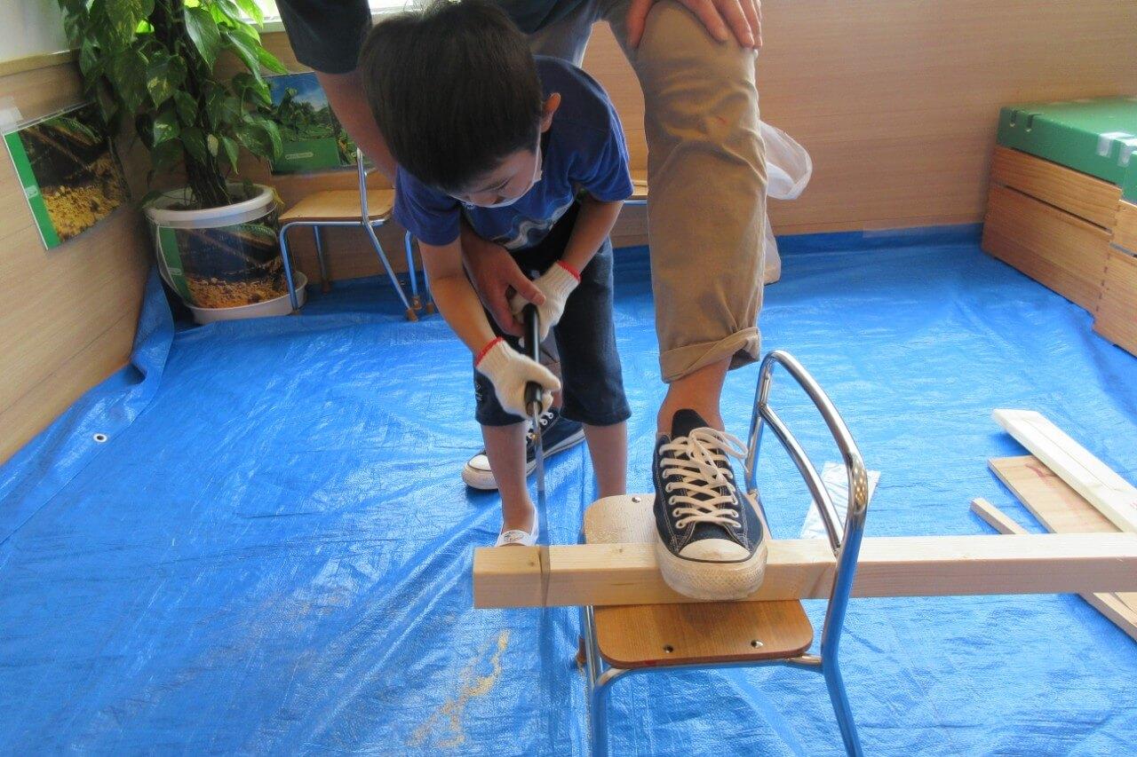 のこぎりで木材を切る子ども