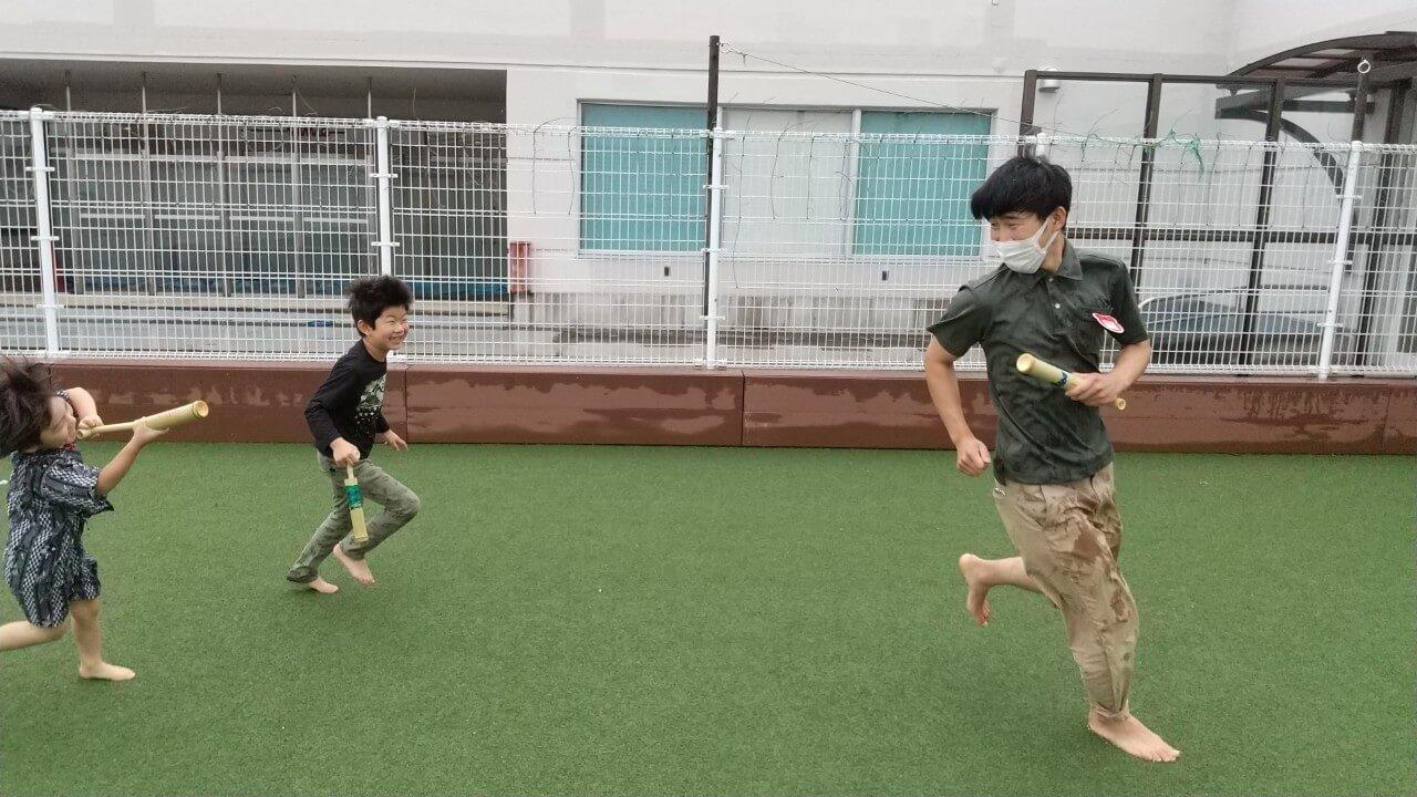 水鉄砲で遊ぶ職員と子ども