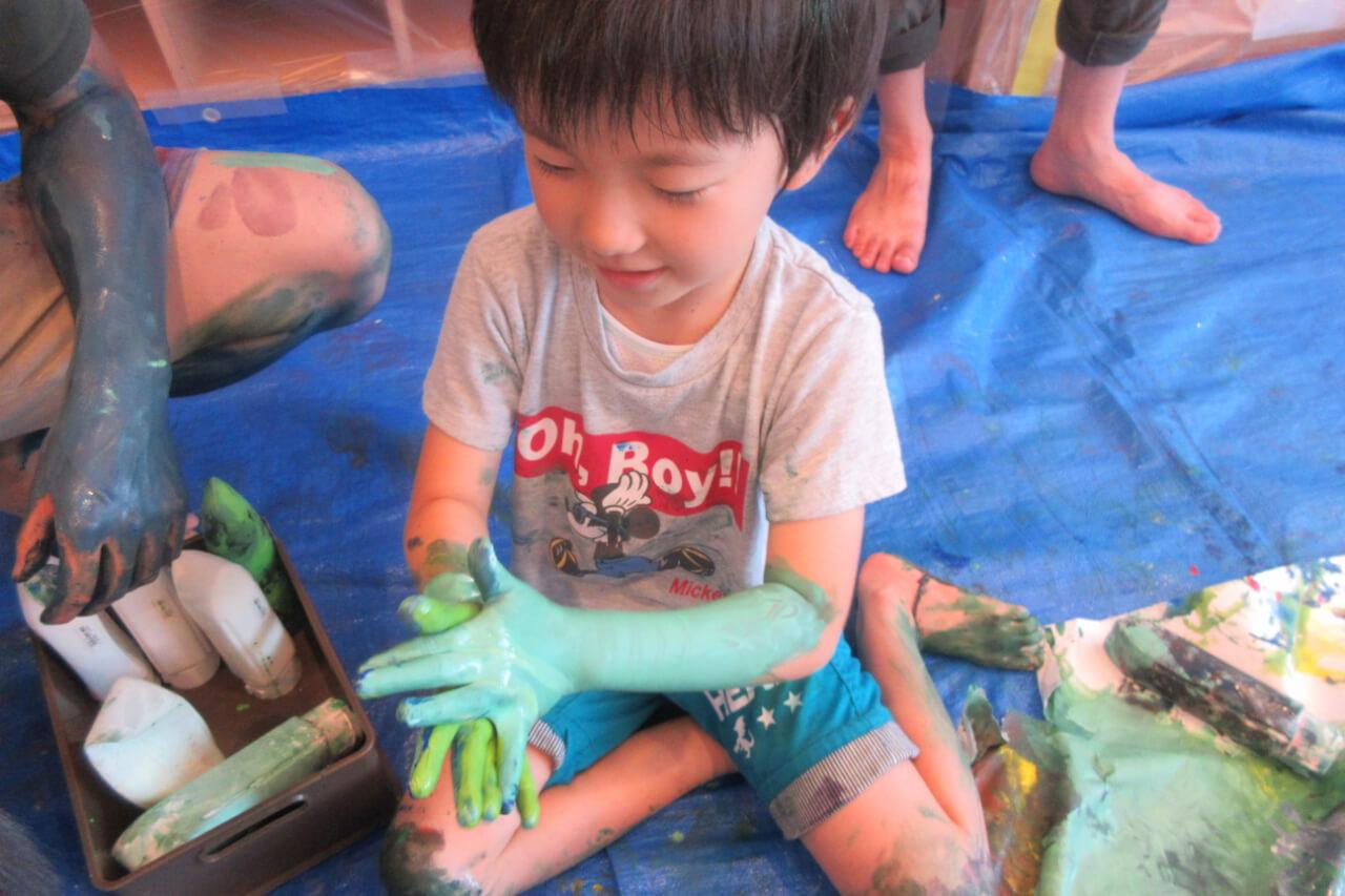 腕を絵具で塗る子ども