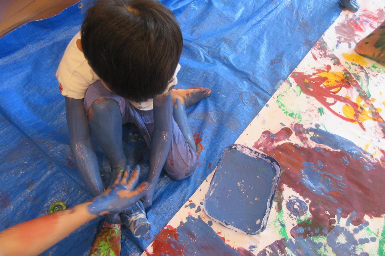 足に絵具を塗る子ども