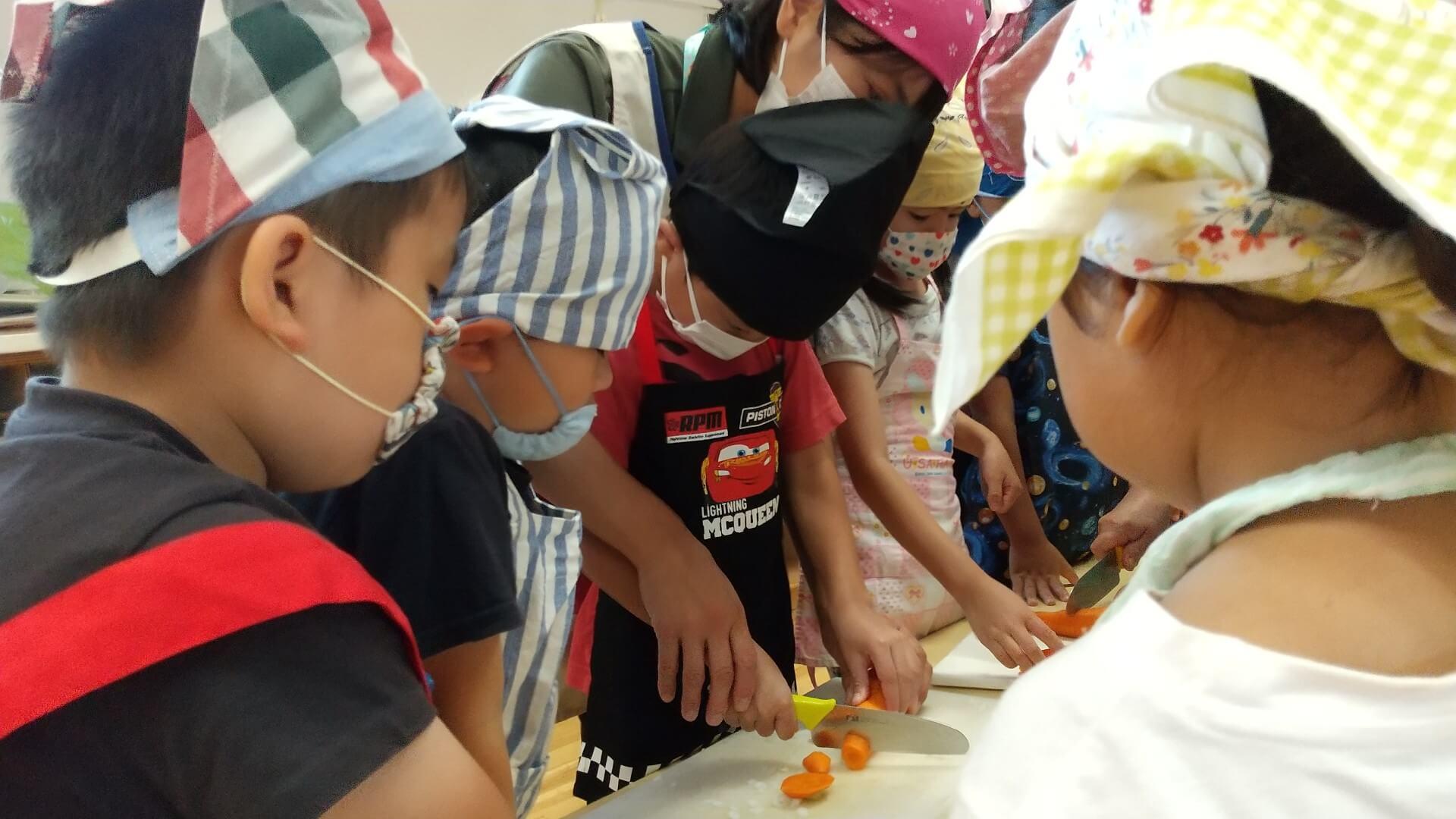 包丁で野菜を切る子ども