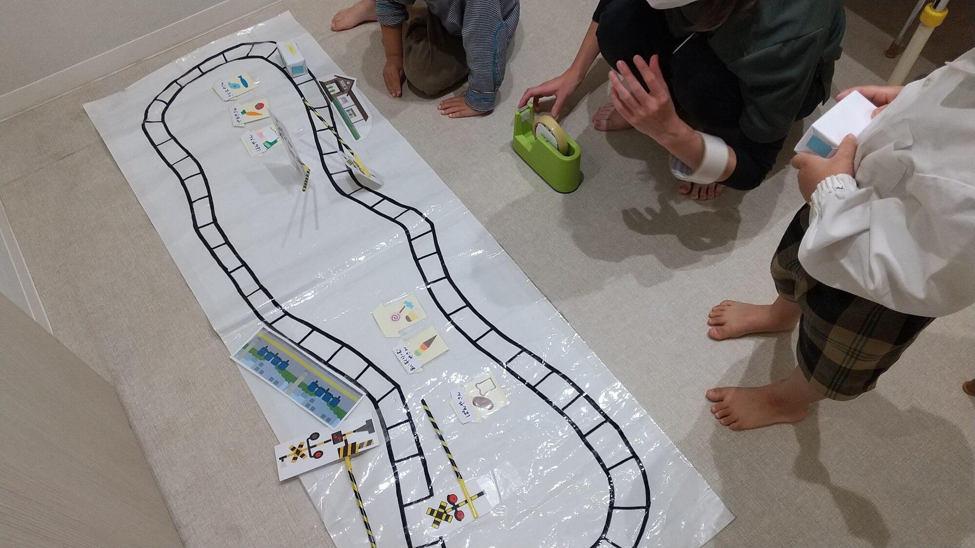 画用紙に描いた線路で遊ぶ子ども