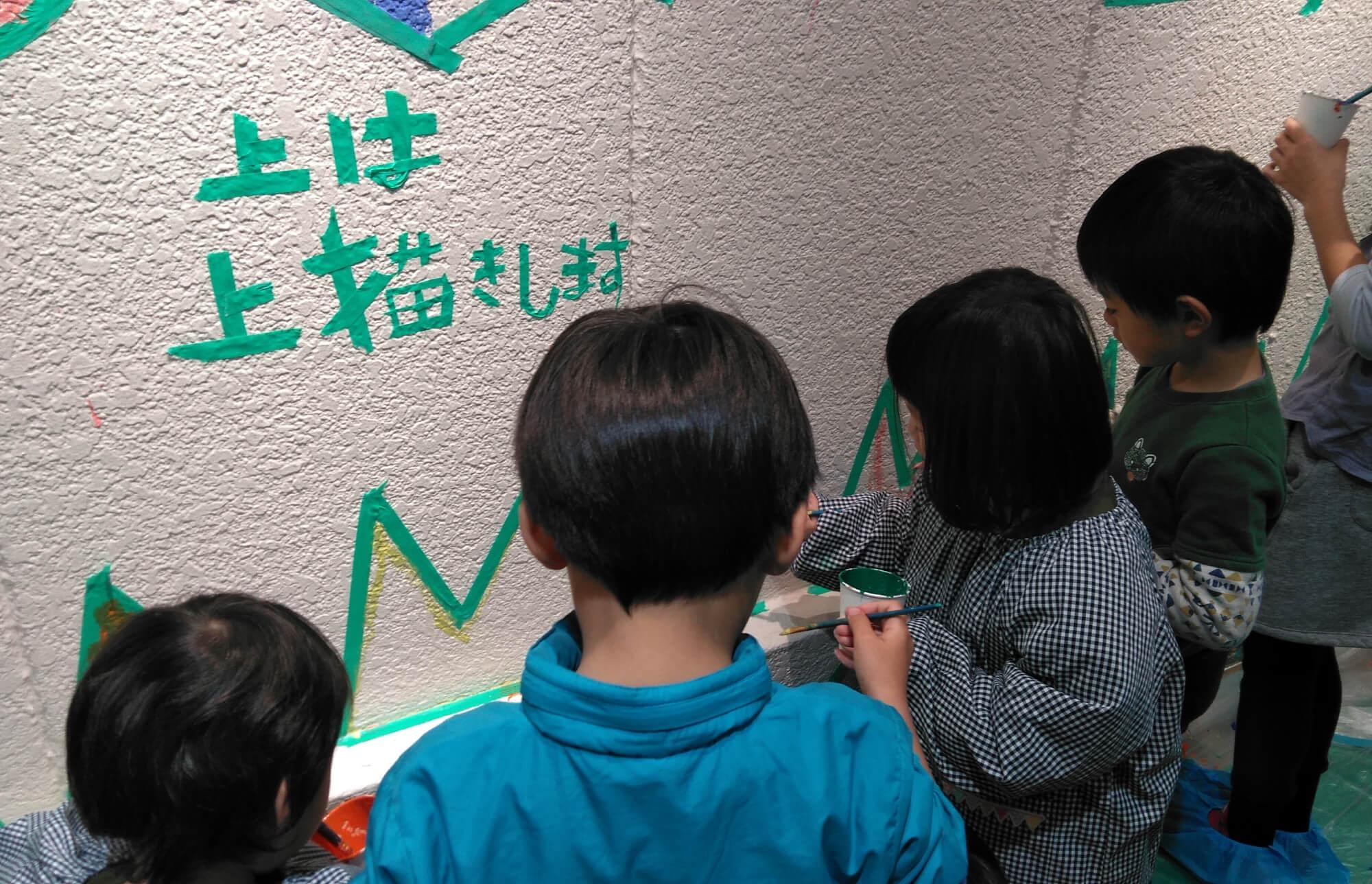壁に色を塗る子どもたち