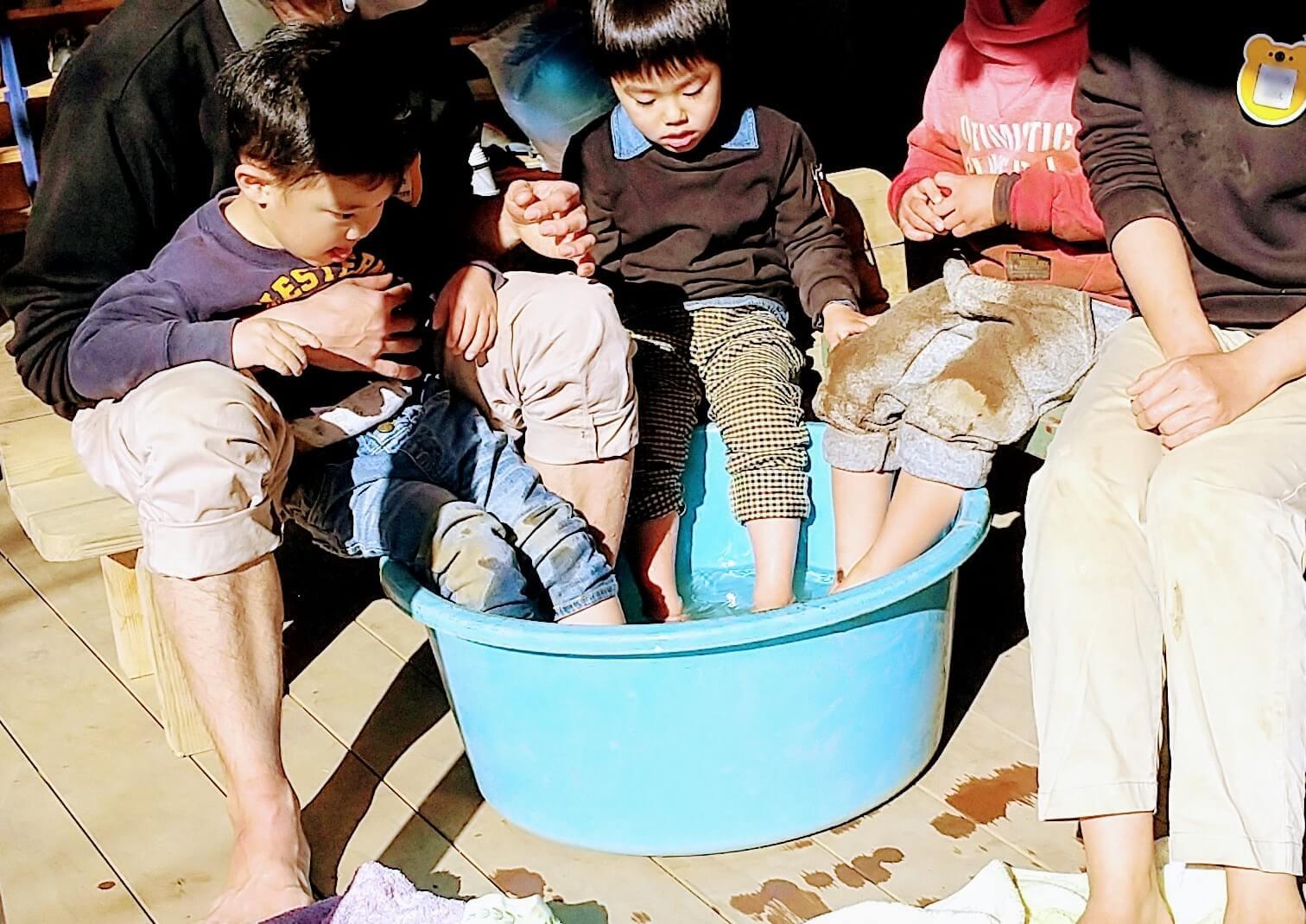 足湯につかる子どもと職員