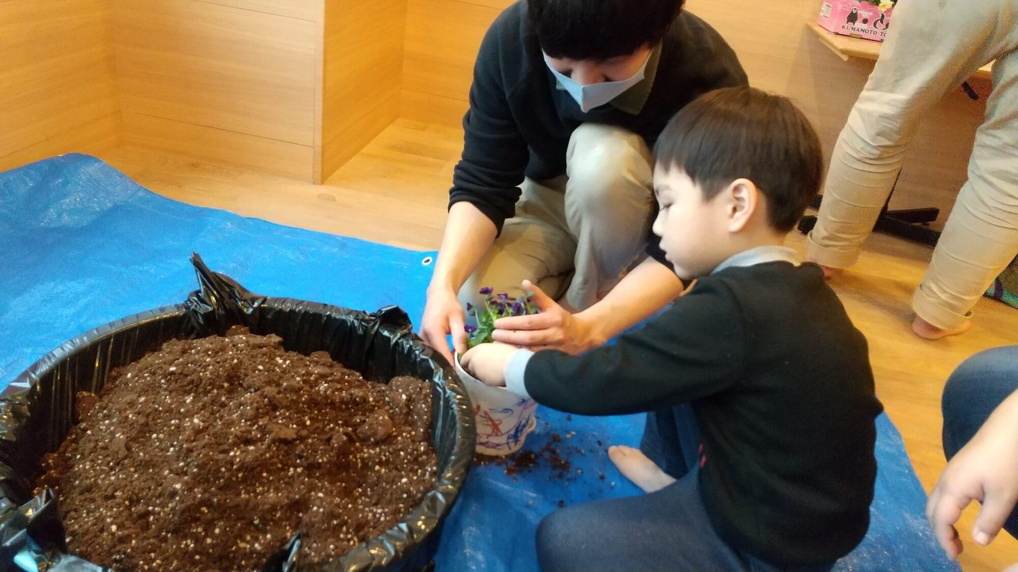 鉢に土を入れる子ども