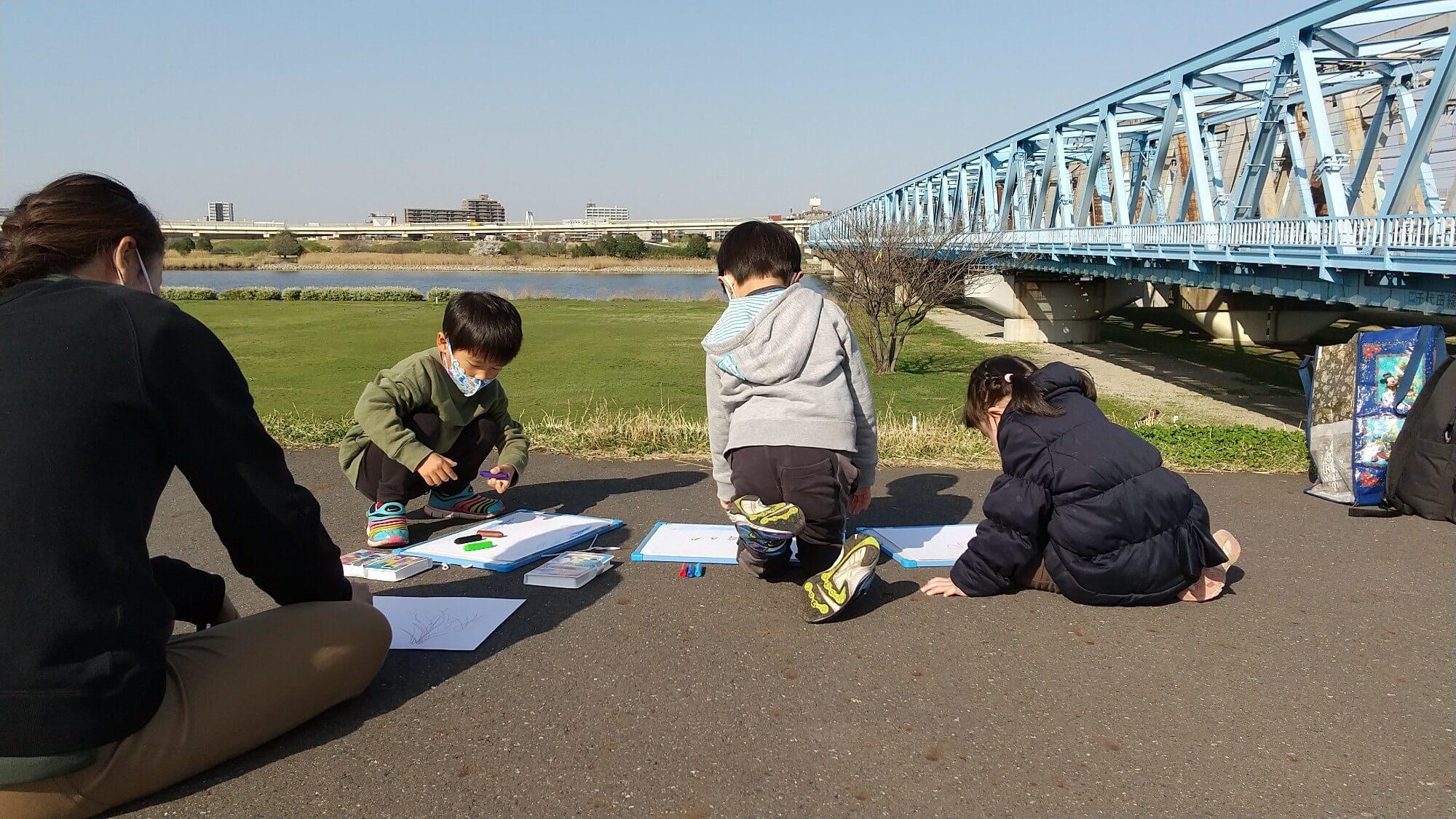 土手で絵を描く子どもたち
