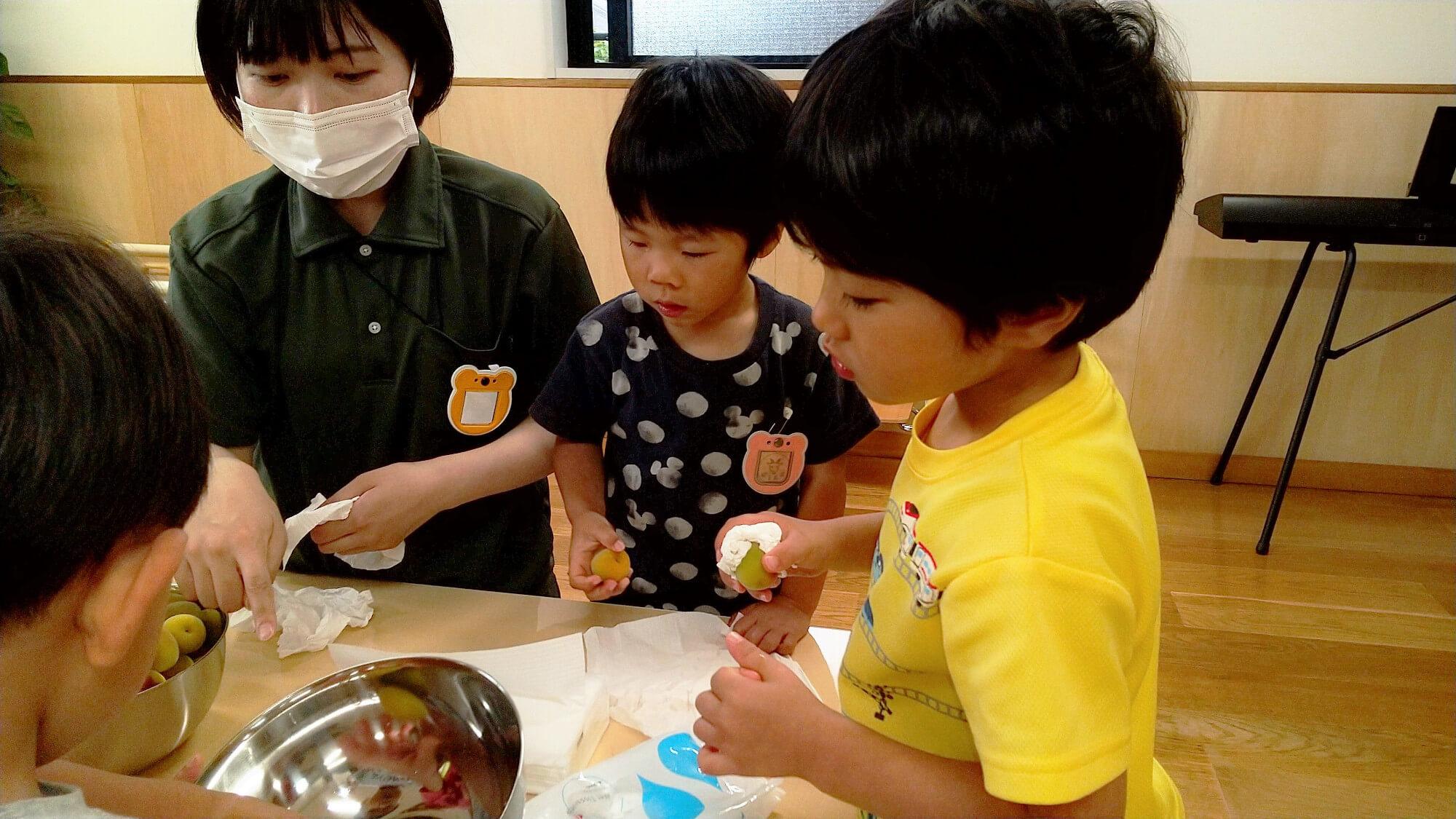 梅の実の拭き方を教え合う子どもたち