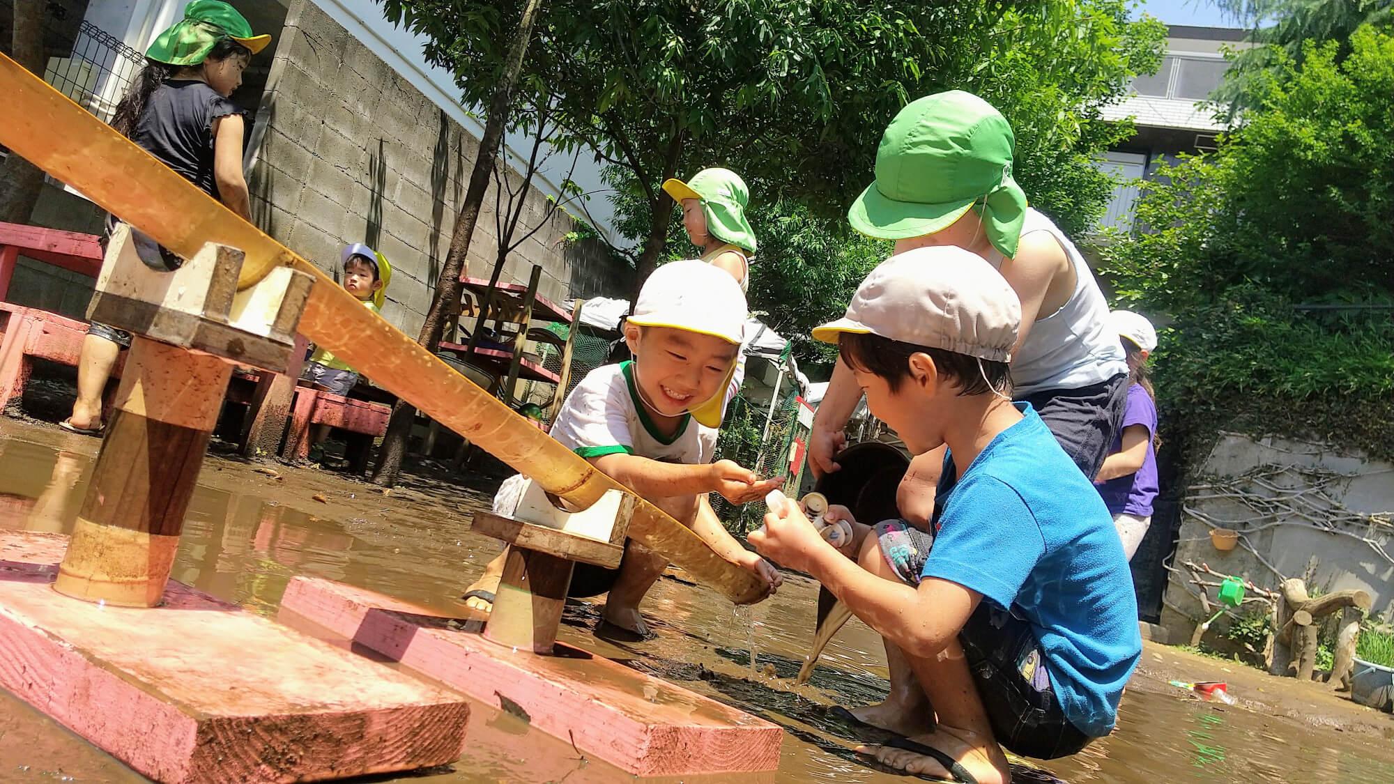 竹の流し台で遊ぶ子どもたち