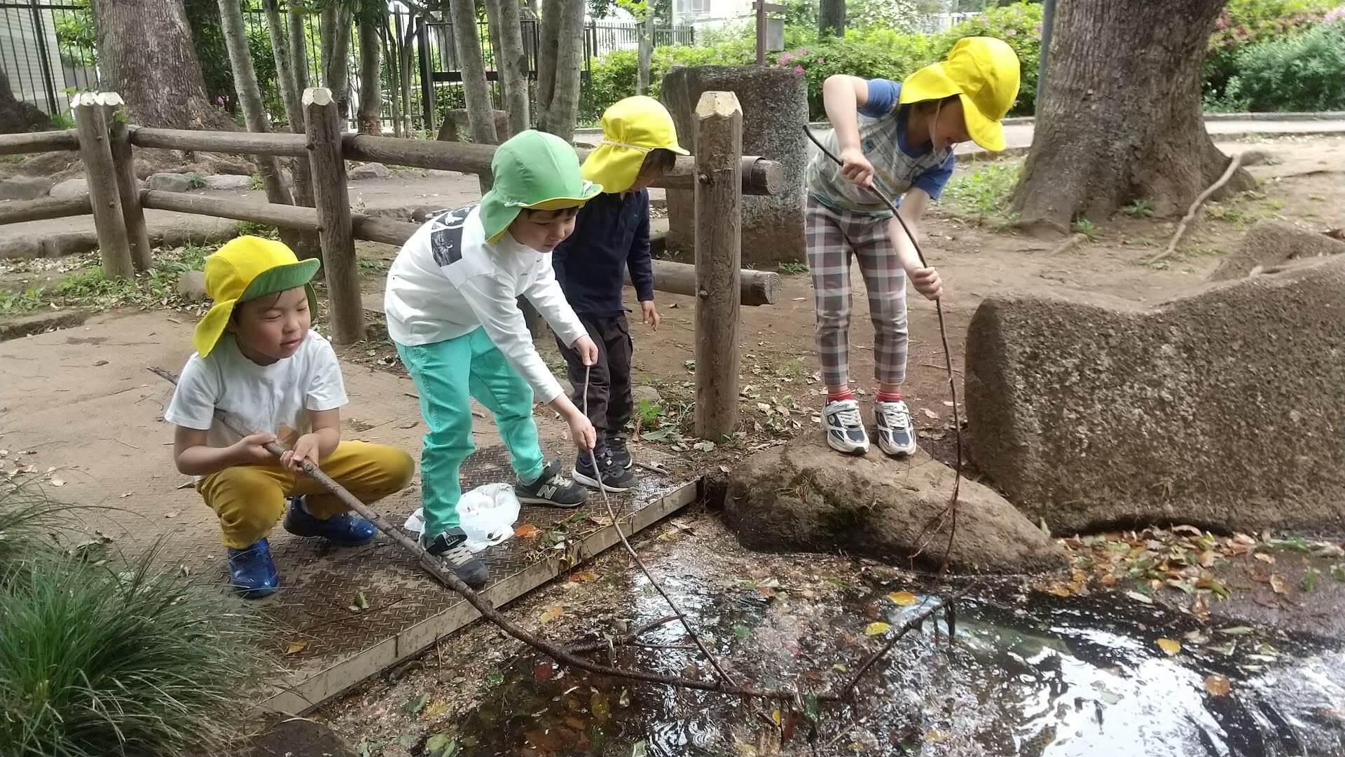 池の水で遊ぶ子ども