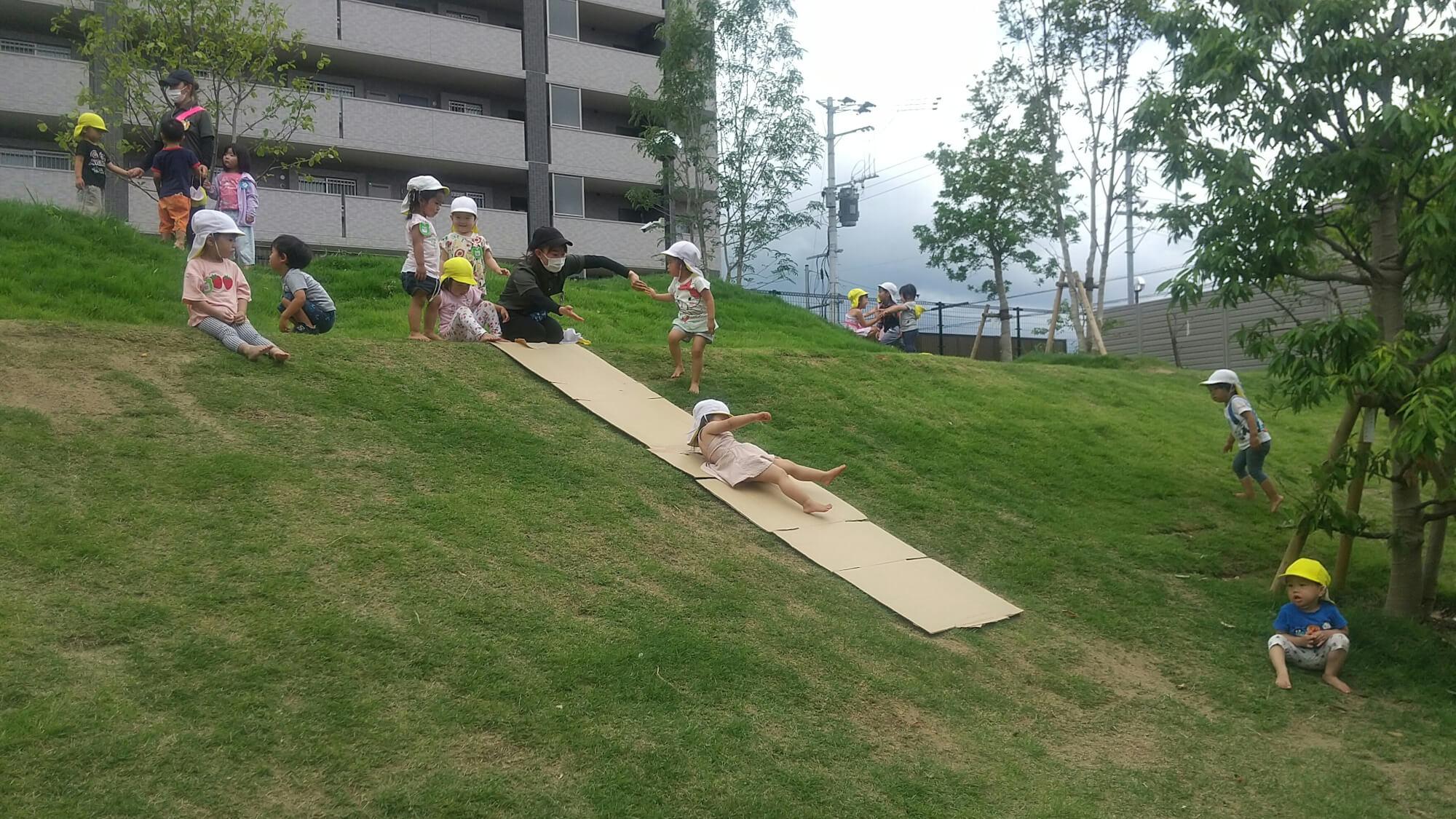 築山を滑り台にして遊ぶ子どもたち