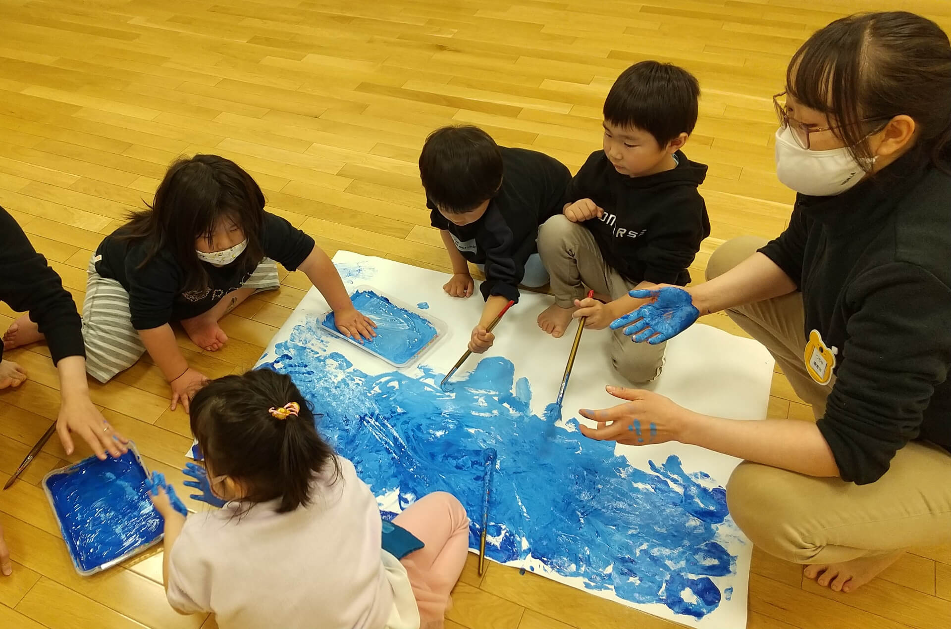 水色の絵の具を塗る子どもたち