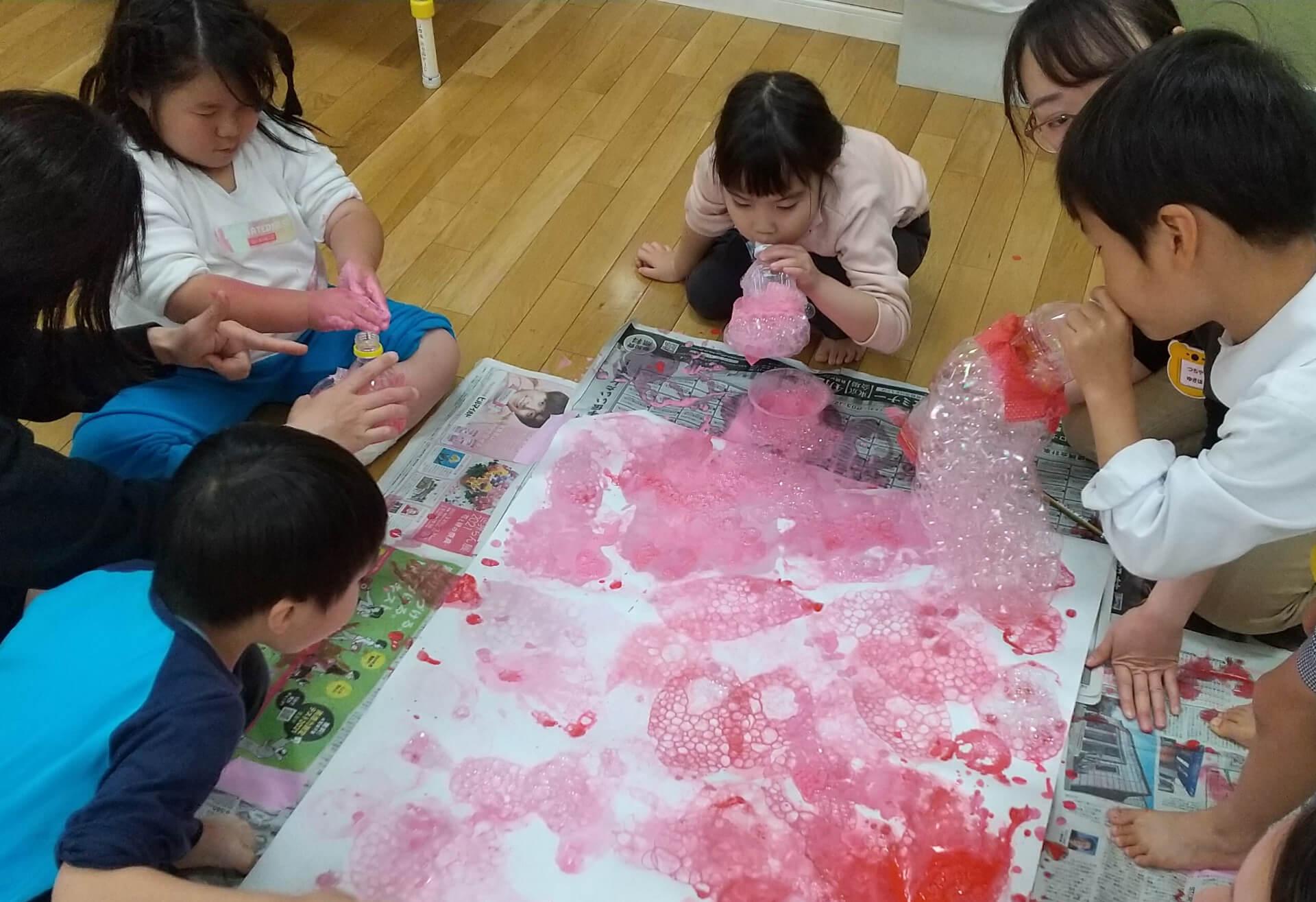 ピンクの絵の具を塗る子どもたち