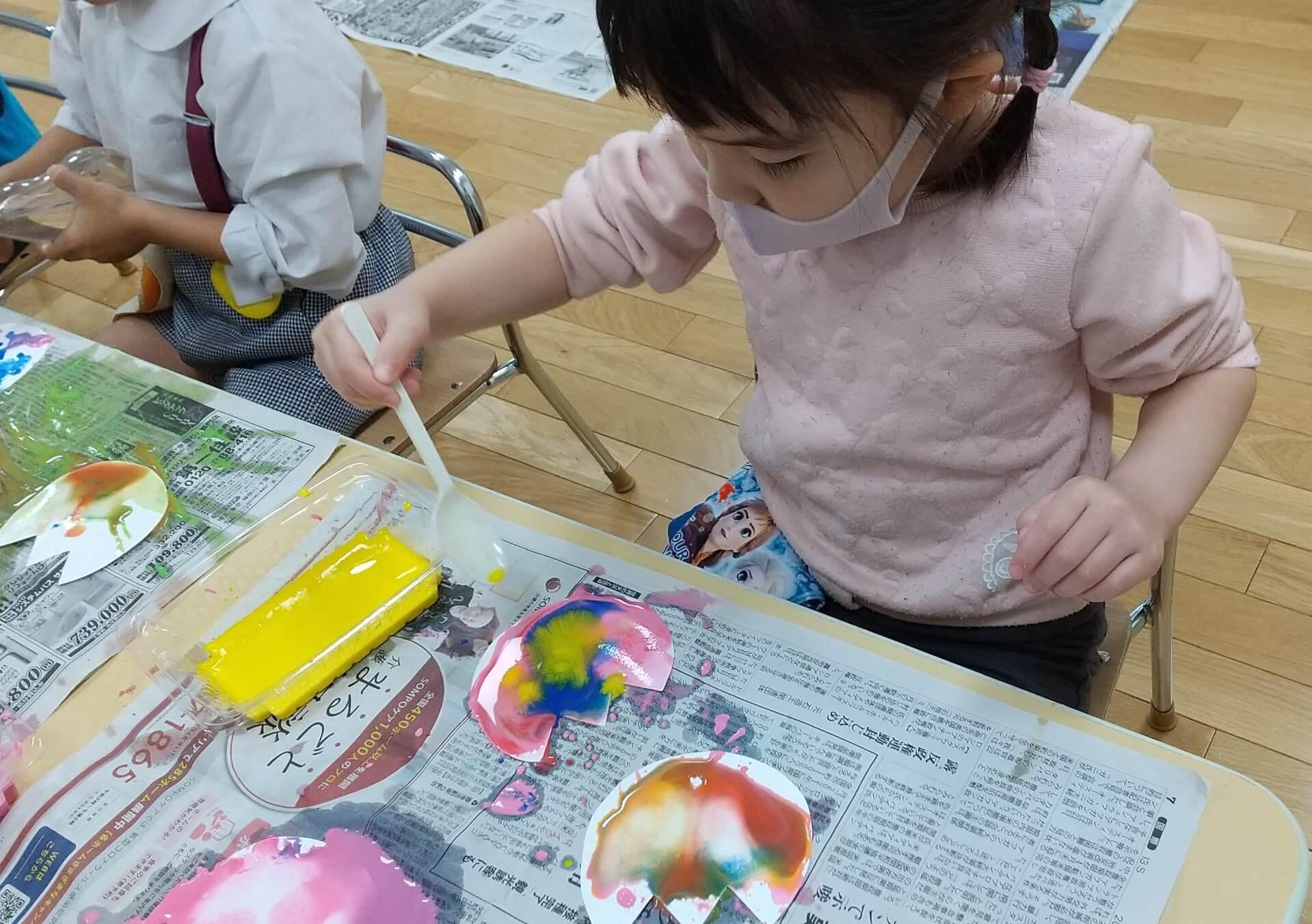 いろんな絵の具を混ぜる子ども