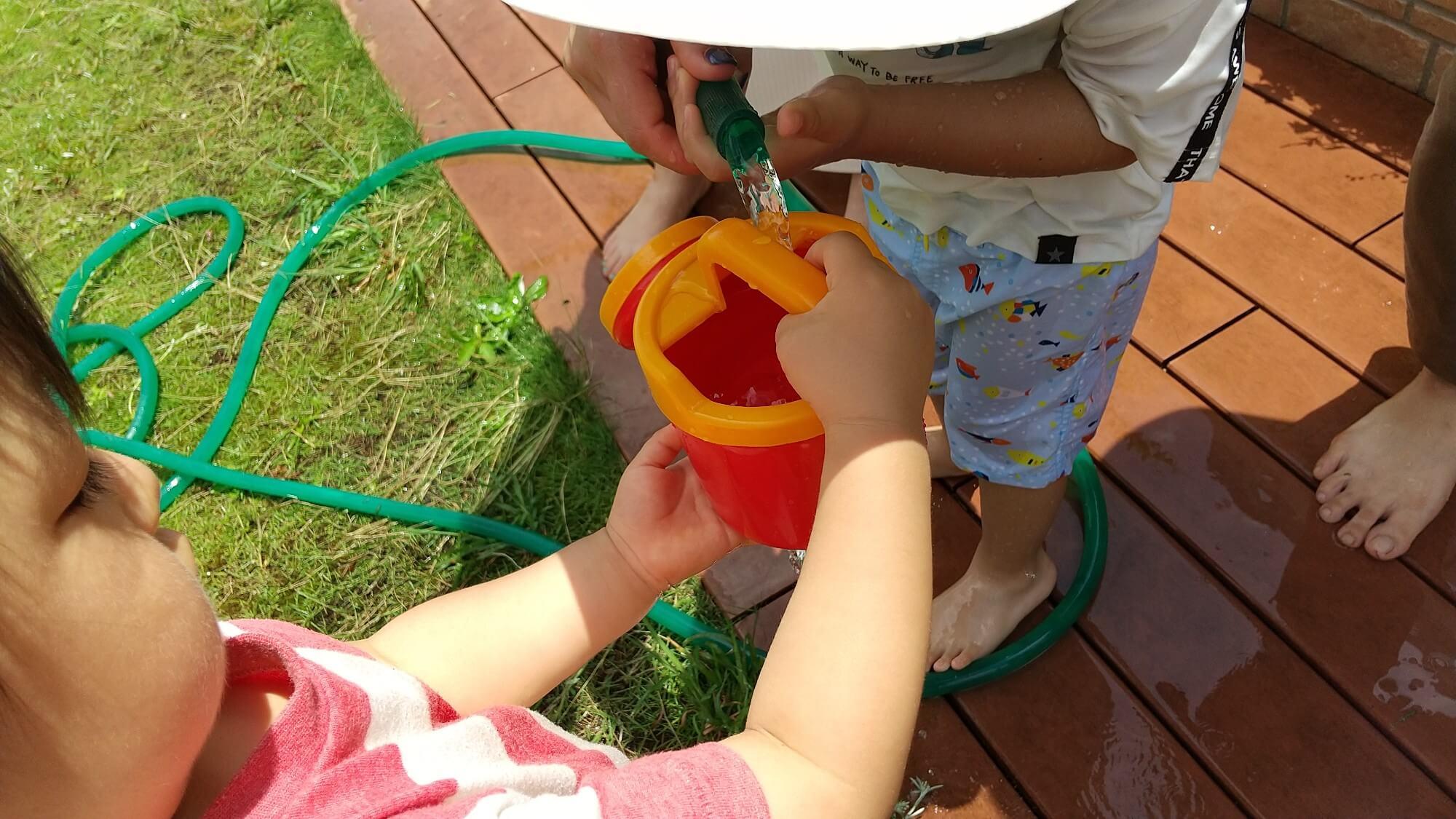 じょうろに水を入れる子どもたち