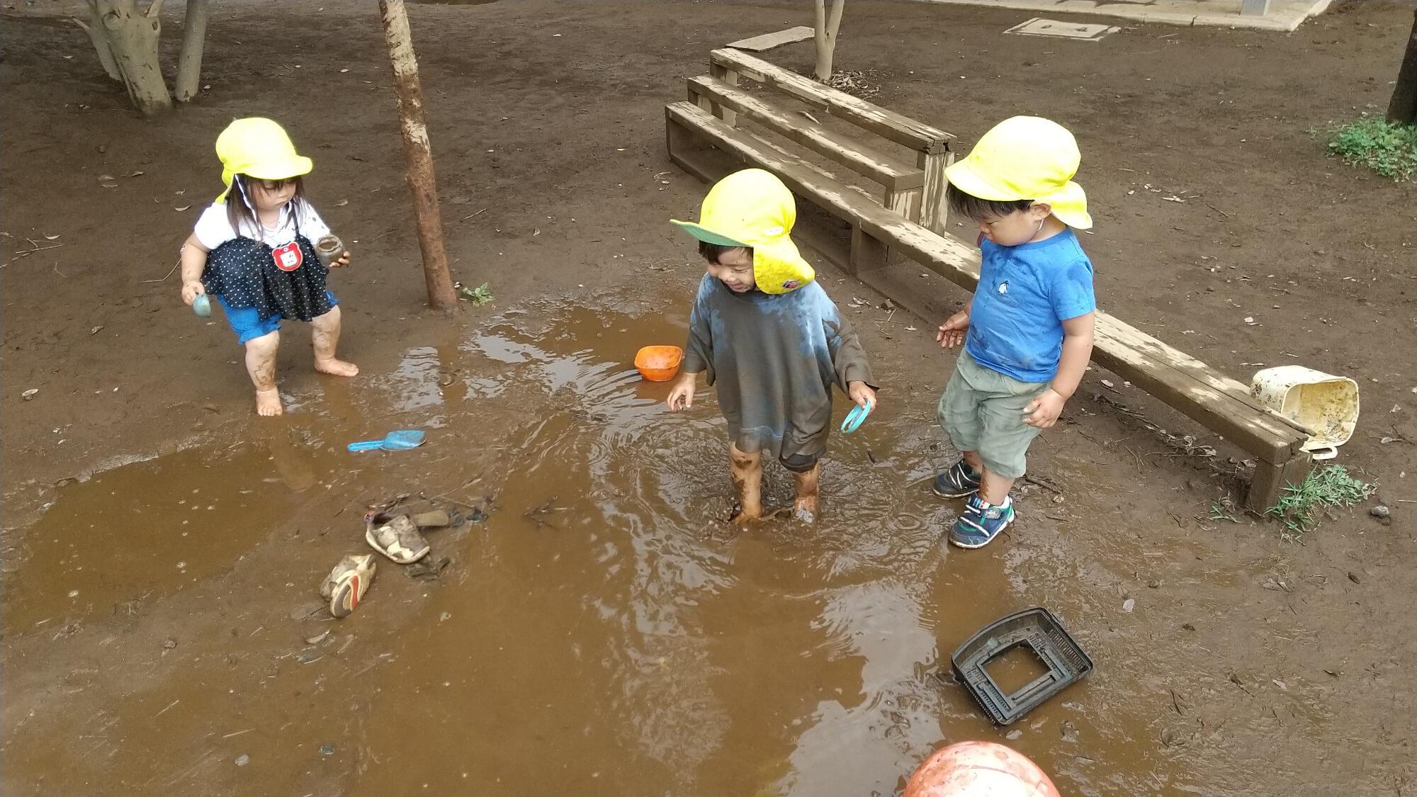 水たまりで泥遊びを楽しむ子どもたち