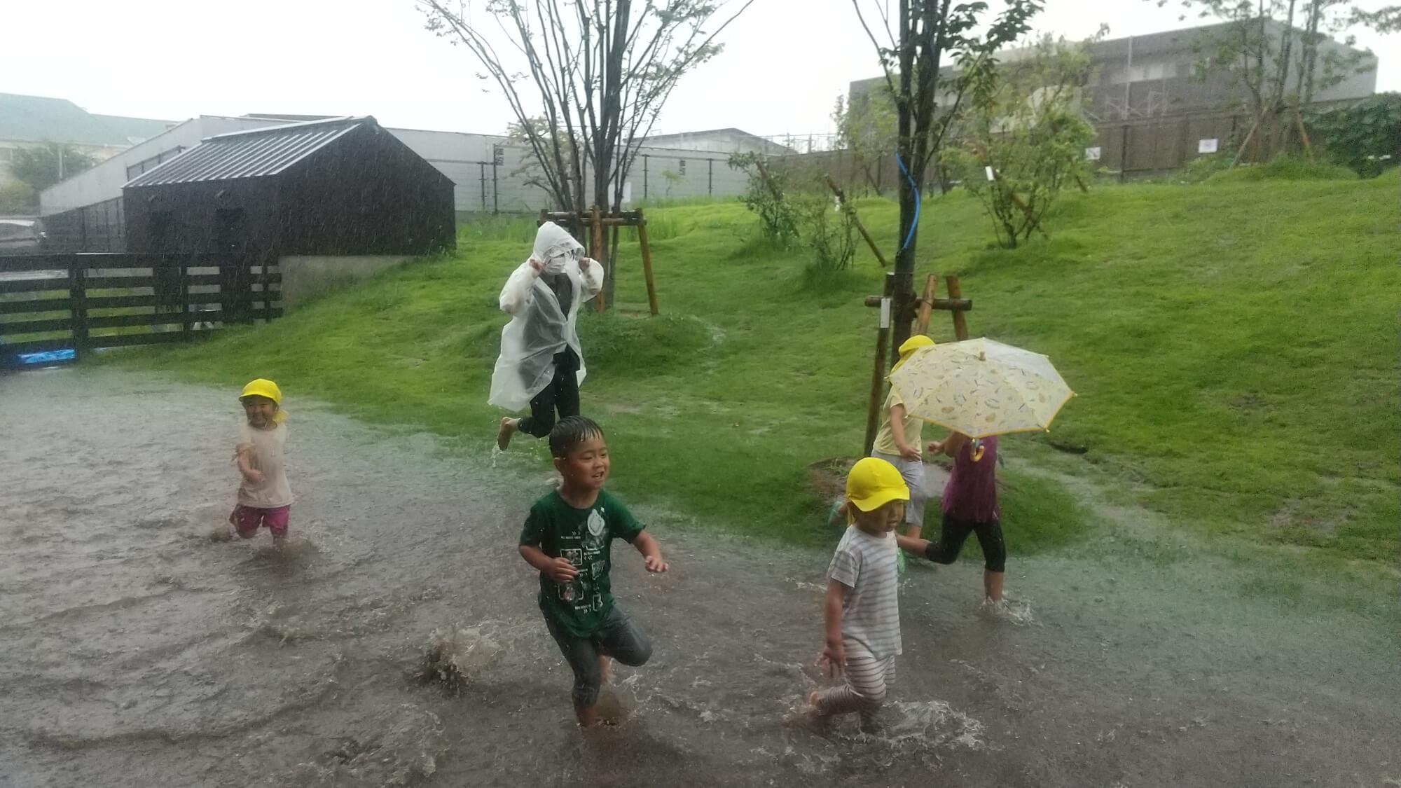 雨の中でかけっこする子どもたち