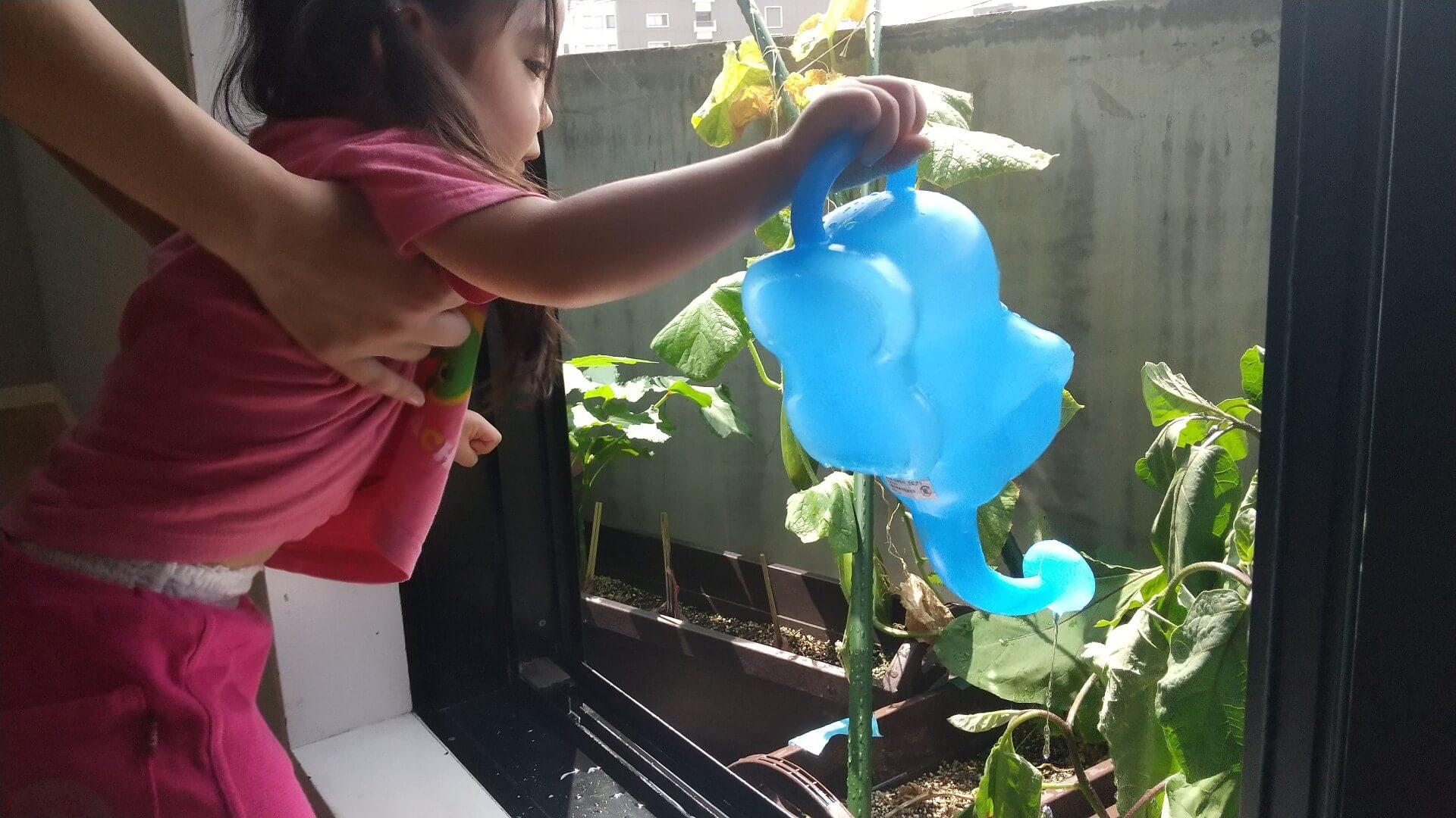 プランターに水をやる子ども