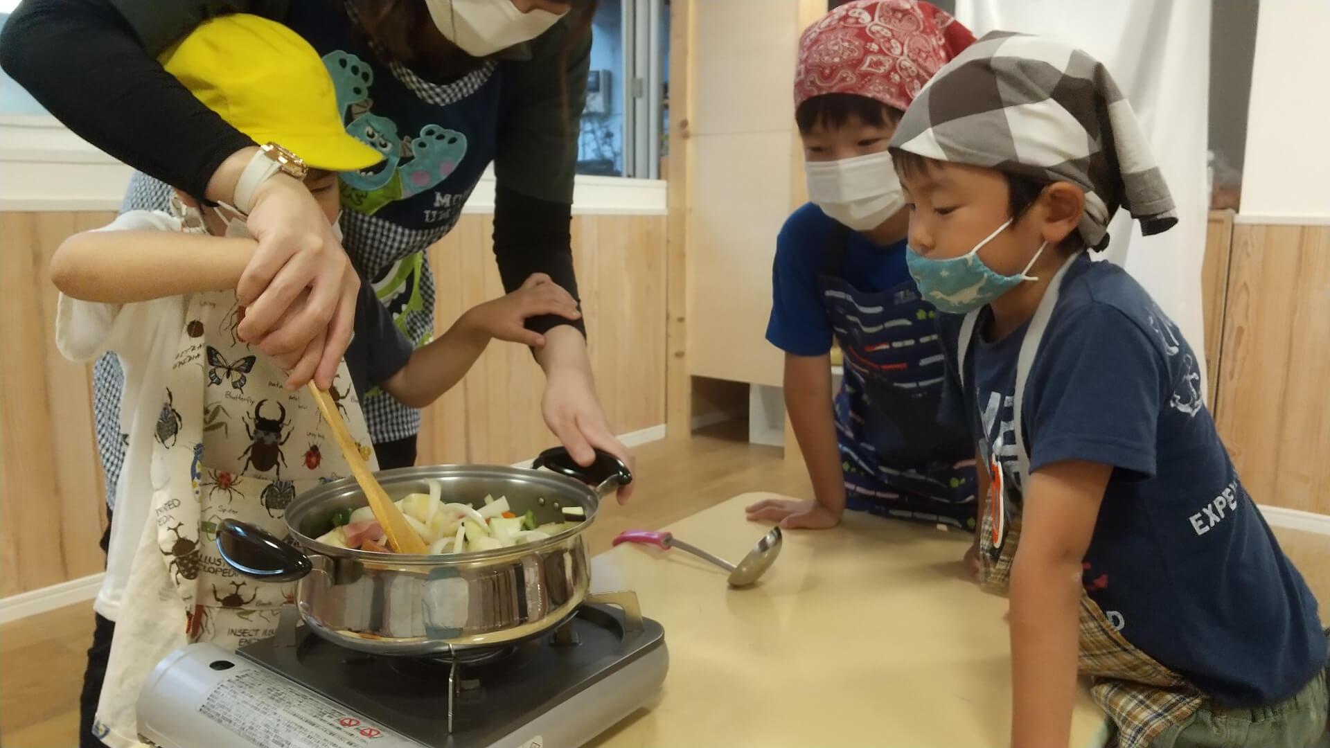 野菜を炒める子どもたち