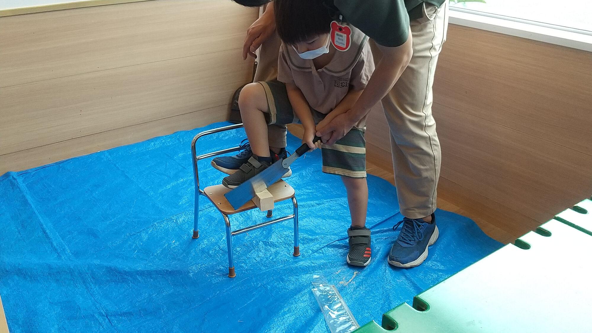 子どもが職員の手を借りながら角材をのこぎりで切る様子