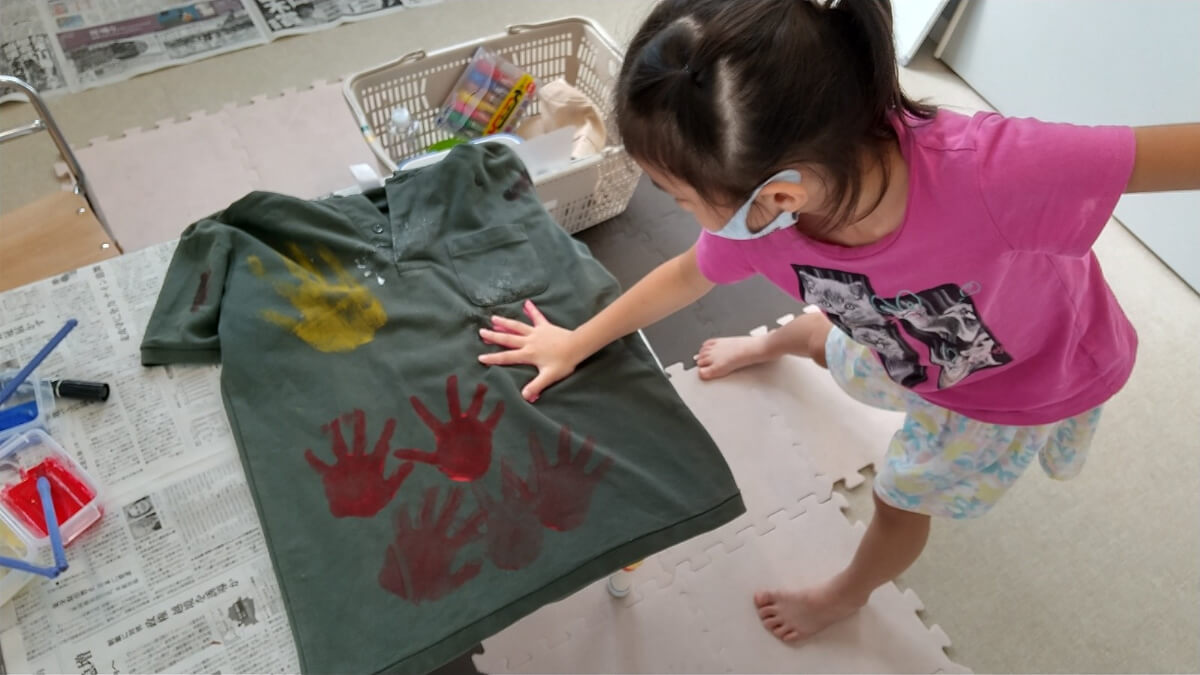 手形スタンプをつける子ども