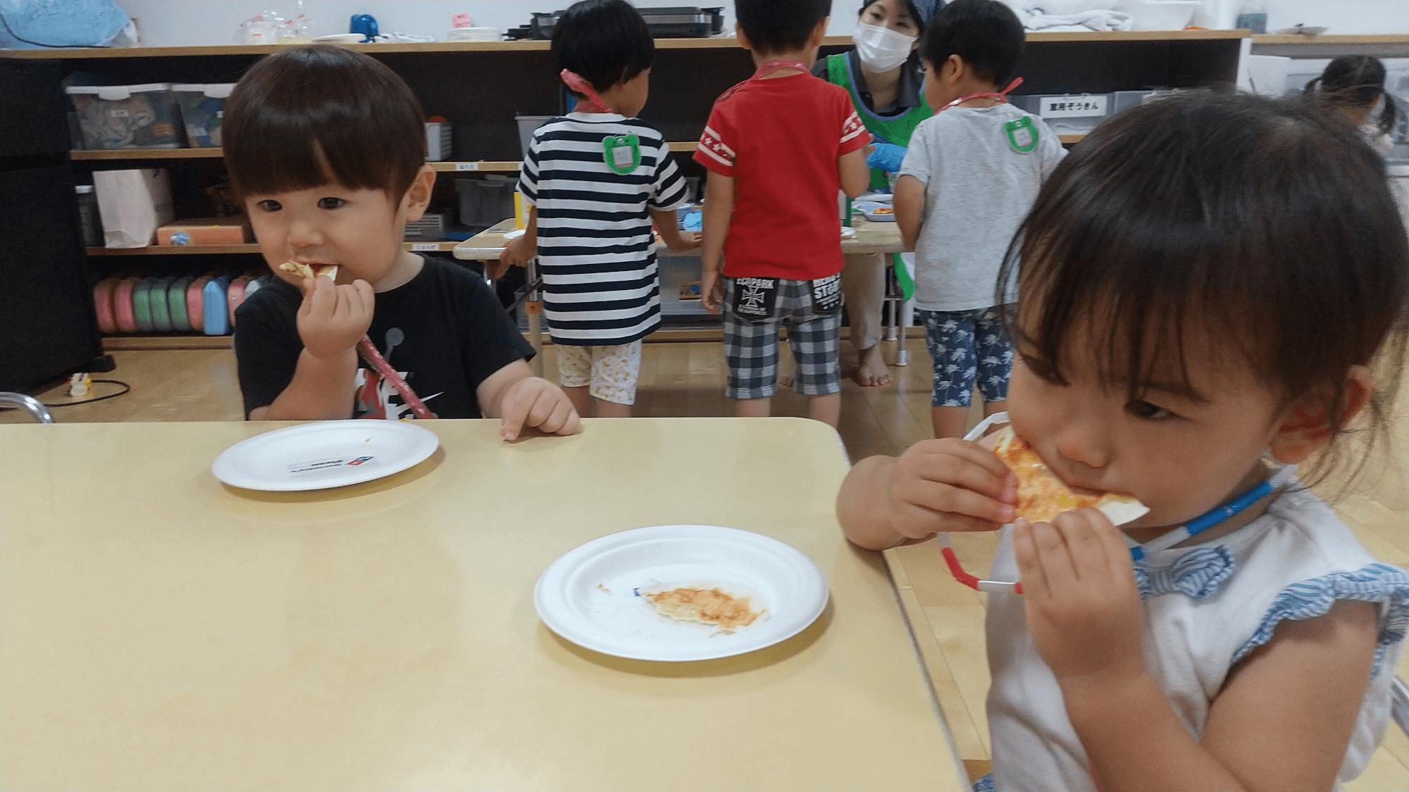 焼きあがったピザを食べる子どもたち