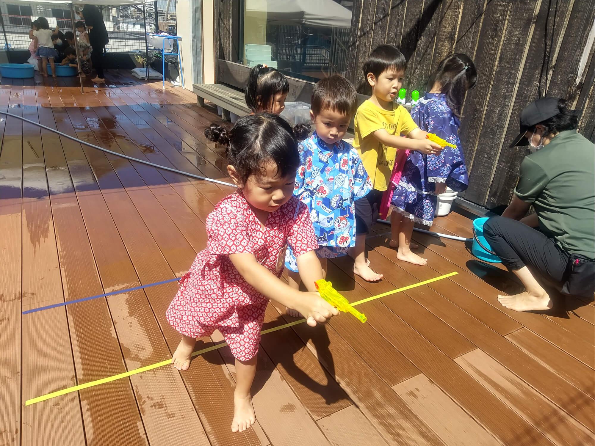 水鉄砲で射的を楽しむ子どもたち